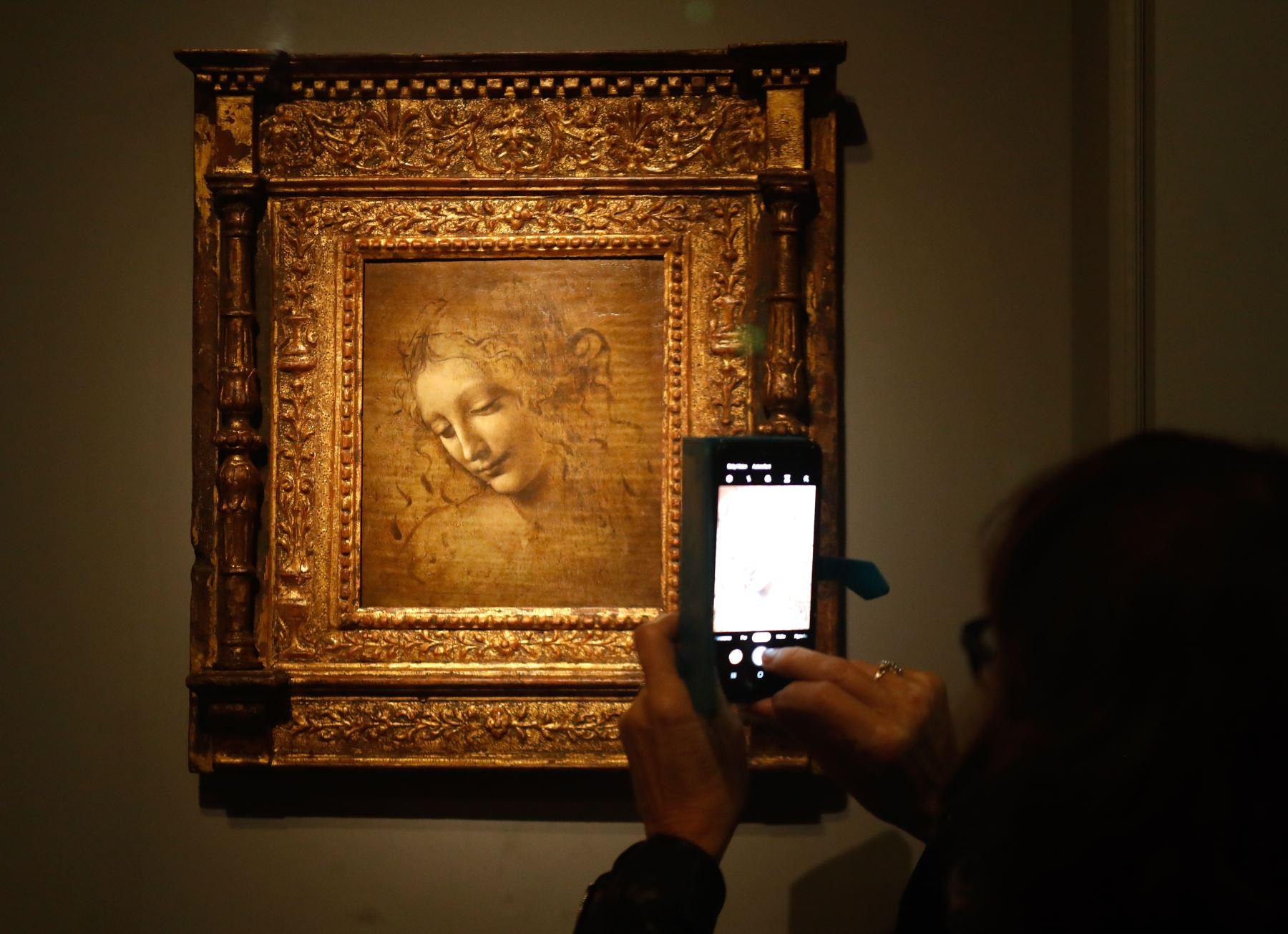 """Una persona toma una fotografía con un teléfono móvil en una pintura al óleo sobre madera de """"La cabeza de una mujer"""" de Leonardo da Vinci, también conocida como La Scapigliata, durante la inauguración de la exposición """"Leonardo da Vinci"""". Foto: AFP"""