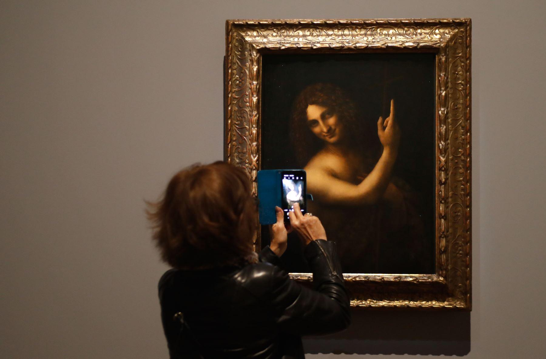 """Una mujer toma una fotografía de una pintura al óleo sobre madera de nogal de """"Saint Jean-Baptiste"""" de Leonardo da Vinci. Foto: AFP"""