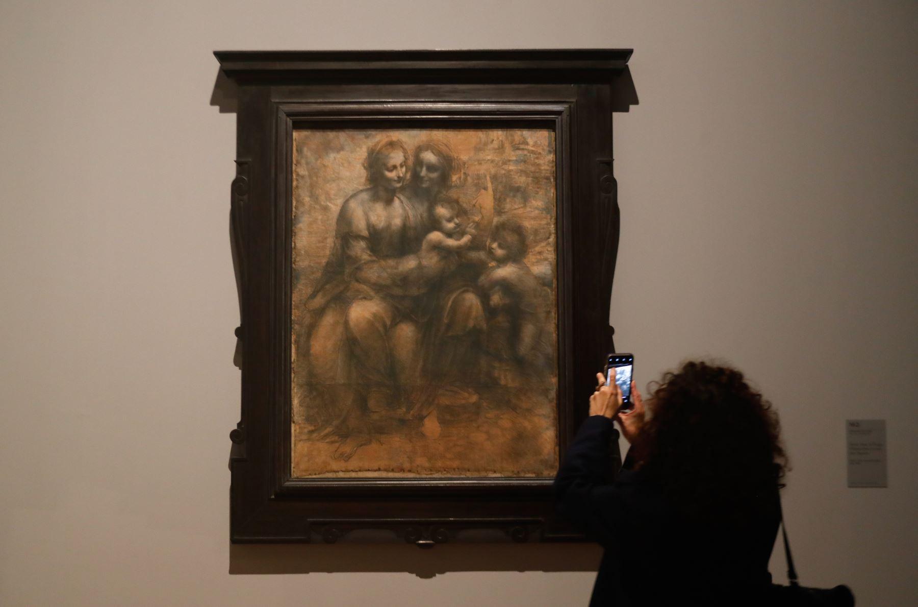 """Una mujer mira un dibujo de """"La Virgen, el Niño Jesús con Santa Ana y San Juan Bautista"""" de Leonardo da Vinci. Foto: AFP"""