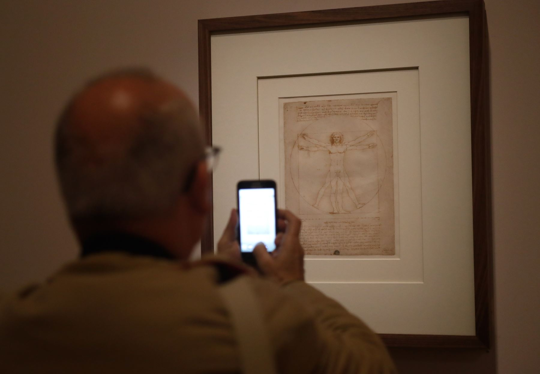 """Un hombre toma una foto con un teléfono móvil en el """"Hombre de Vitruvio"""", el famoso dibujo anotado, realizado alrededor de 1490 con pluma, tinta y lavado sobre papel, por Leonardo da Vinci. Foto: AFP"""
