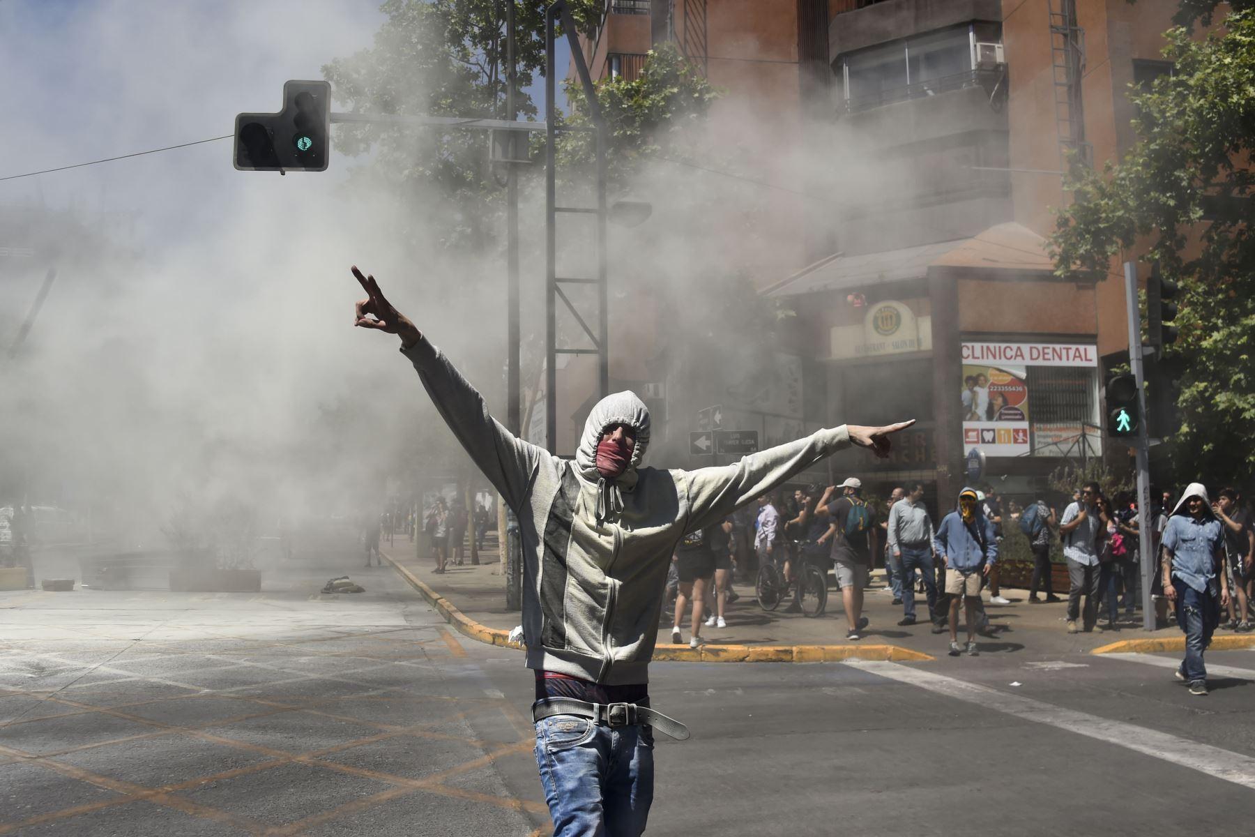 Un manifestante encapuchado participa en una protesta contra las políticas del gobierno cerca del Centro Costanera, un complejo comercial en Santiago. Foto: AFP