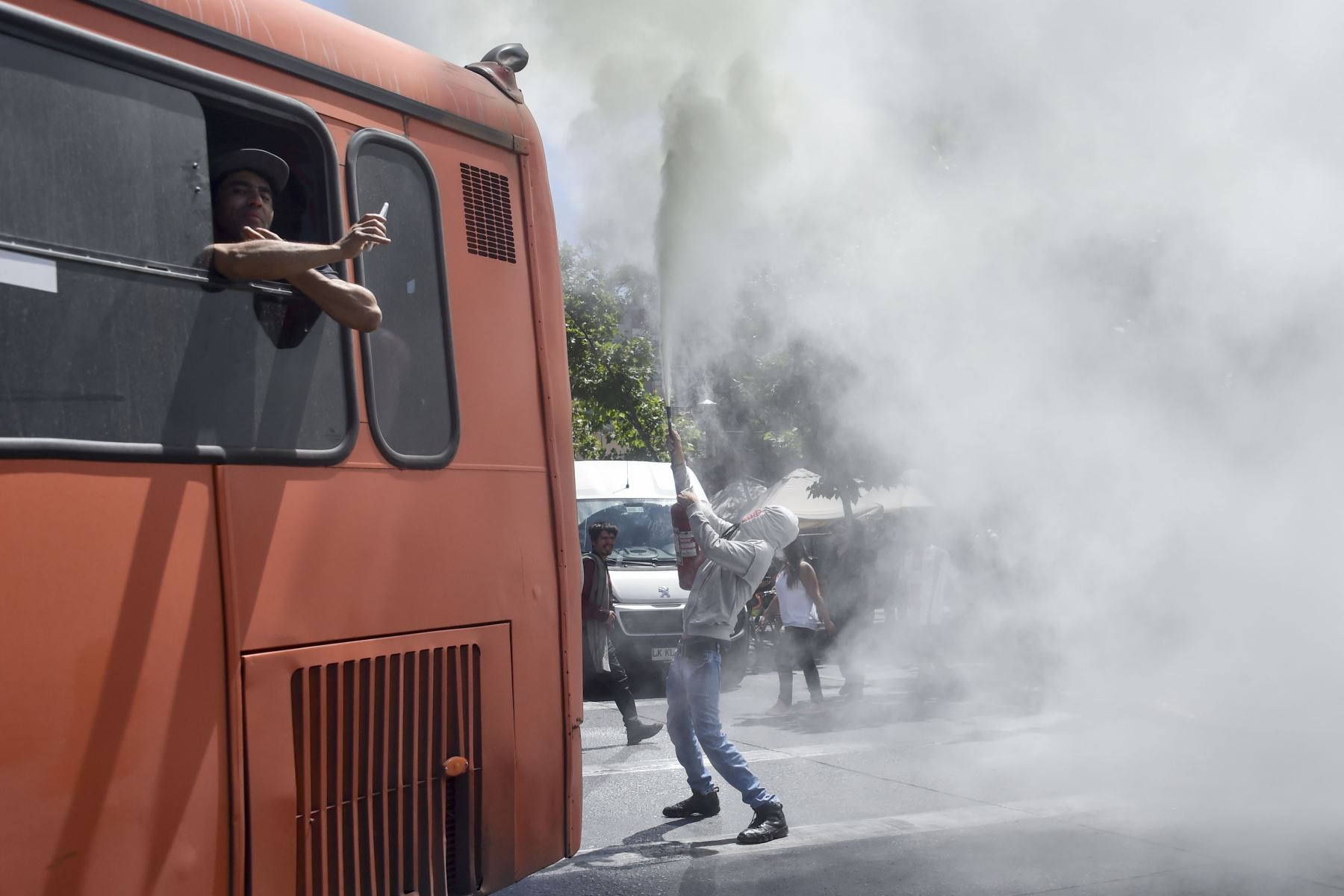 Un manifestante desencadena un extintor de incendios durante una protesta contra las políticas gubernamentales cerca del Centro Costanera, un complejo comercial en Santiago. Foto: AFP