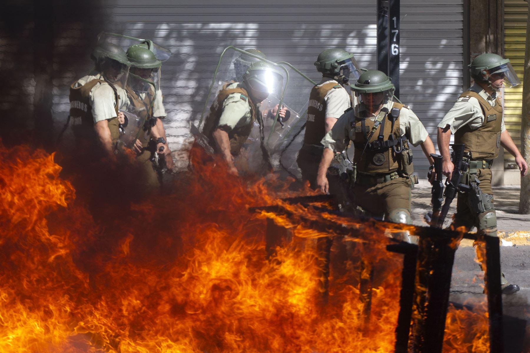 La policía antidisturbios pasó junto a una barricada en llamas durante una protesta contra las políticas económicas del gobierno en Santiago. Foto: AFP