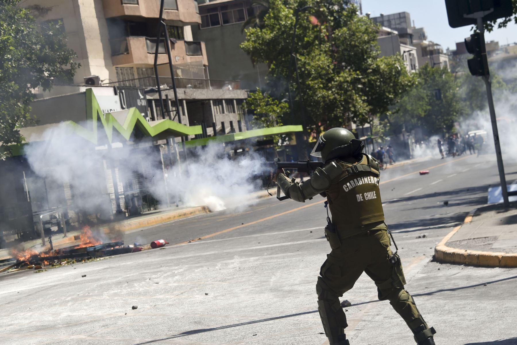 Un miembro de la policía antidisturbios disparó contra los manifestantes durante una protesta contra las políticas económicas del gobierno, cerca del Centro Costanera en Santiago. Foto:AFP