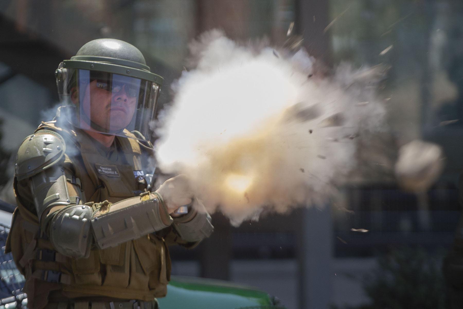 Un oficial de la policía antidisturbios lanza gases lacrimógenos para dispersar a los manifestantes durante una protesta contra las políticas económicas del gobierno, cerca del Centro Costanera. Foto: AFP