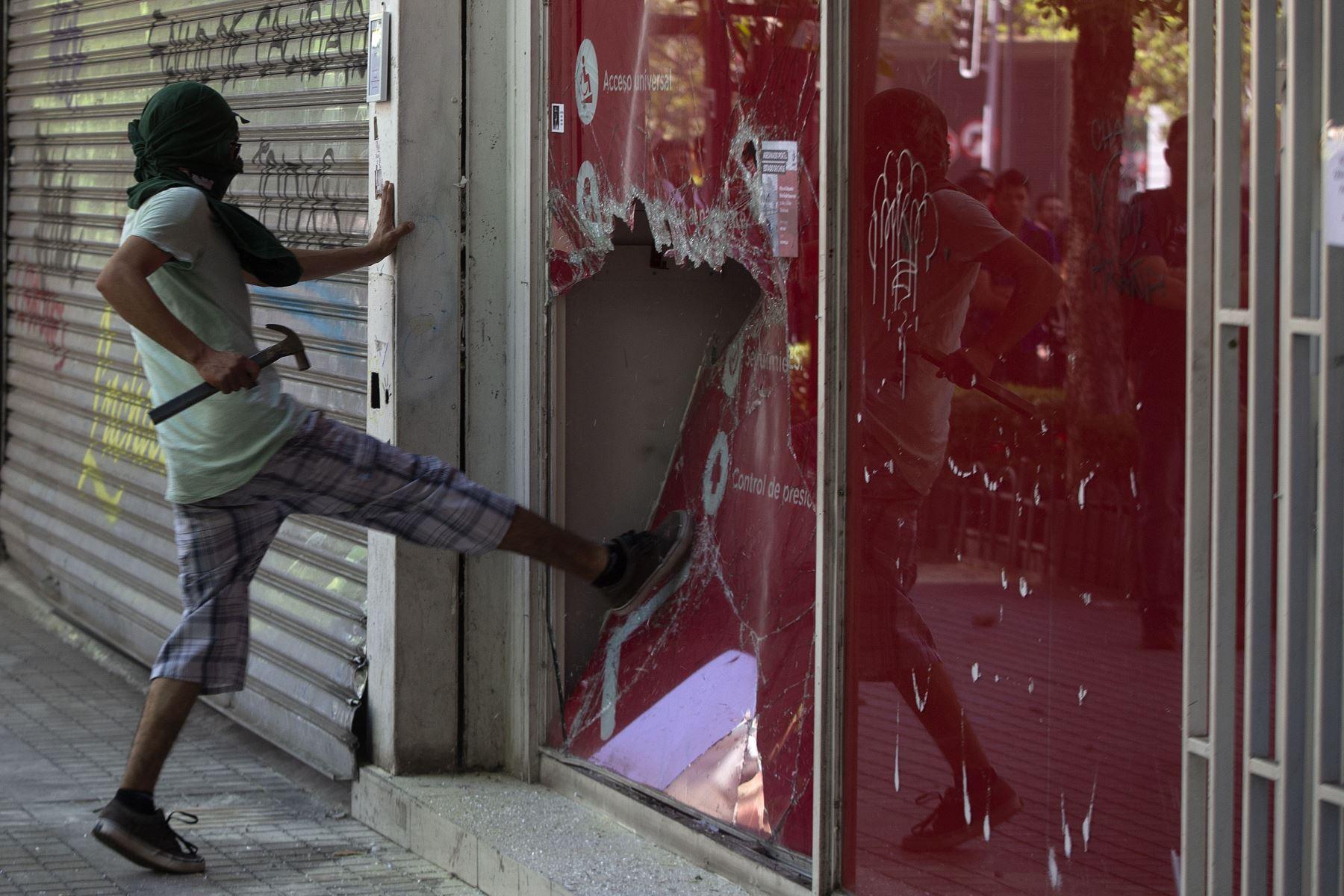 Un manifestante rompe una ventana durante una protesta contra las políticas económicas del gobierno en Chile en Santiago. Foto:AFP