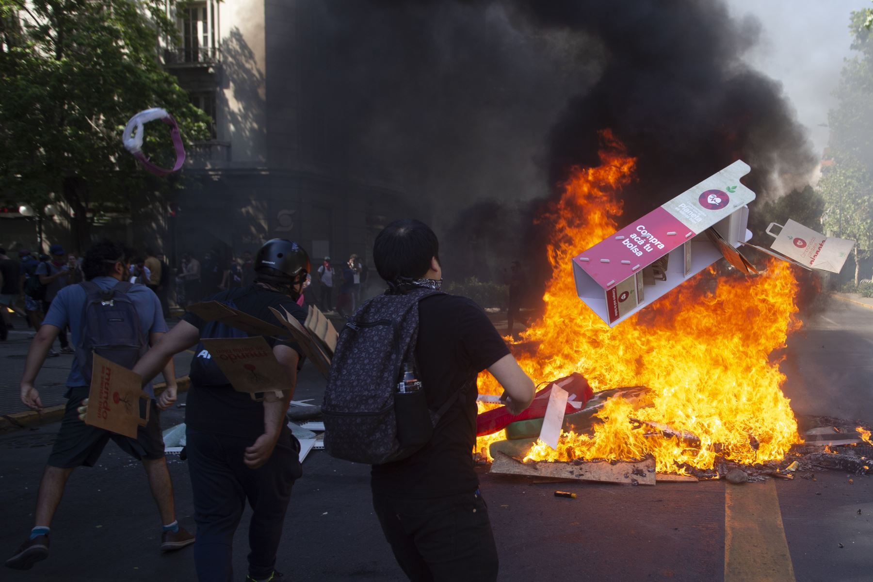 Los manifestantes arrojan cartón para quemar en una hoguera durante una protesta contra las políticas económicas del gobierno en Santiago. Foto: AFP