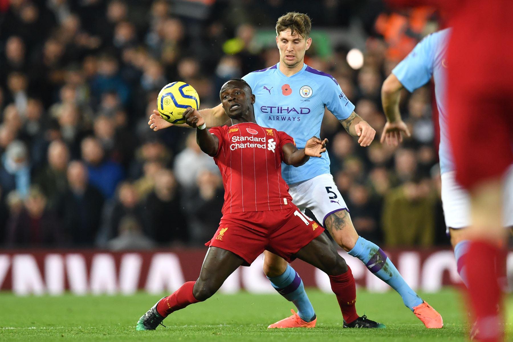 El delantero senegalés del Liverpool Sadio Mane  compite con el defensor inglés del Manchester City John Stones durante el partido de fútbol de la Premier League inglesa entre Liverpool y Manchester City. Foto: AFP