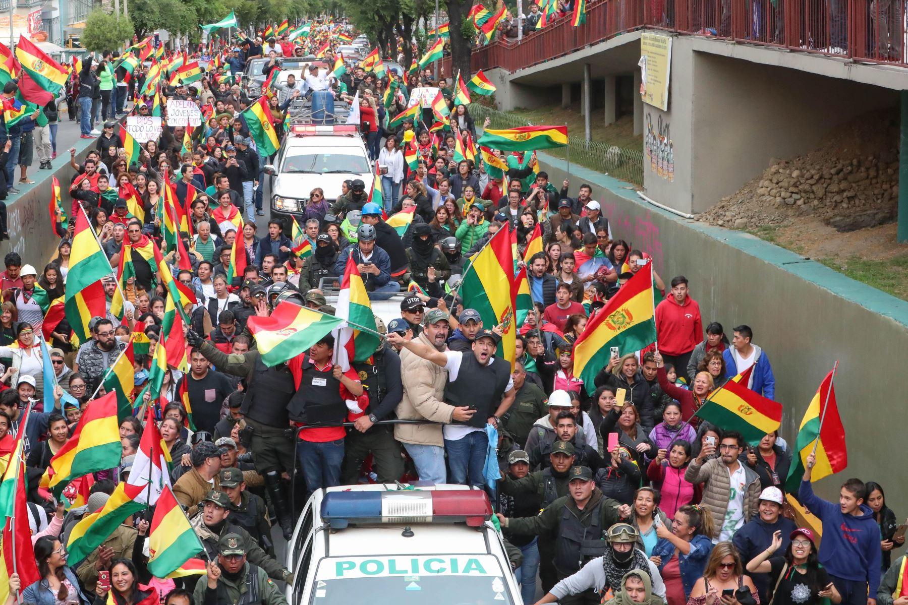 El líder cívico cruceño Luis Fernando Camacho (d) y el potosino Marco Pumari (i), celebran junto a ciudadanos bolivianos la renuncia del presidente de Bolivia, Evo Morales. Foto: AFP