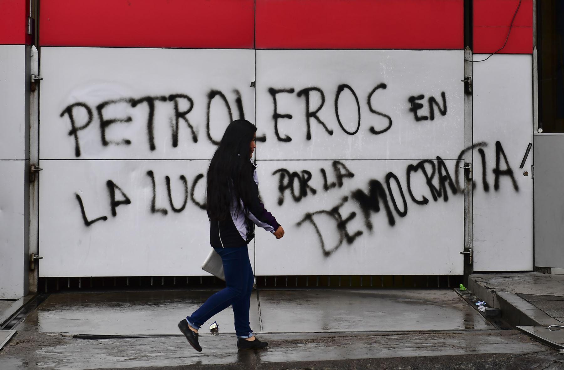 """Una mujer camina junto a una pared con un graffiti que dice """"Productores de petróleo en la lucha por la democracia"""" en La Paz. Foto: AFP"""