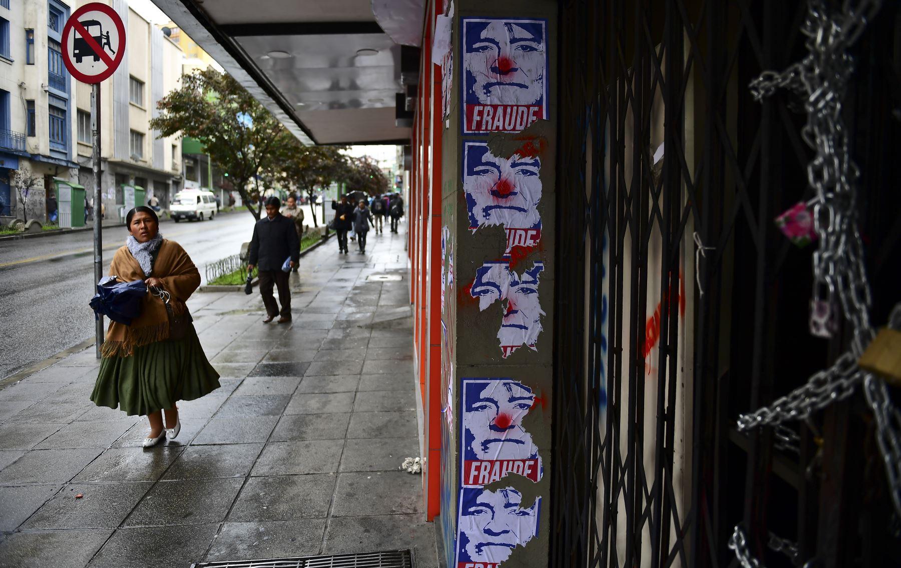 Una mujer camina junto a la pared con carteles del ex presidente boliviano Evo Morales representado como un payaso en La Paz. Foto: AFP