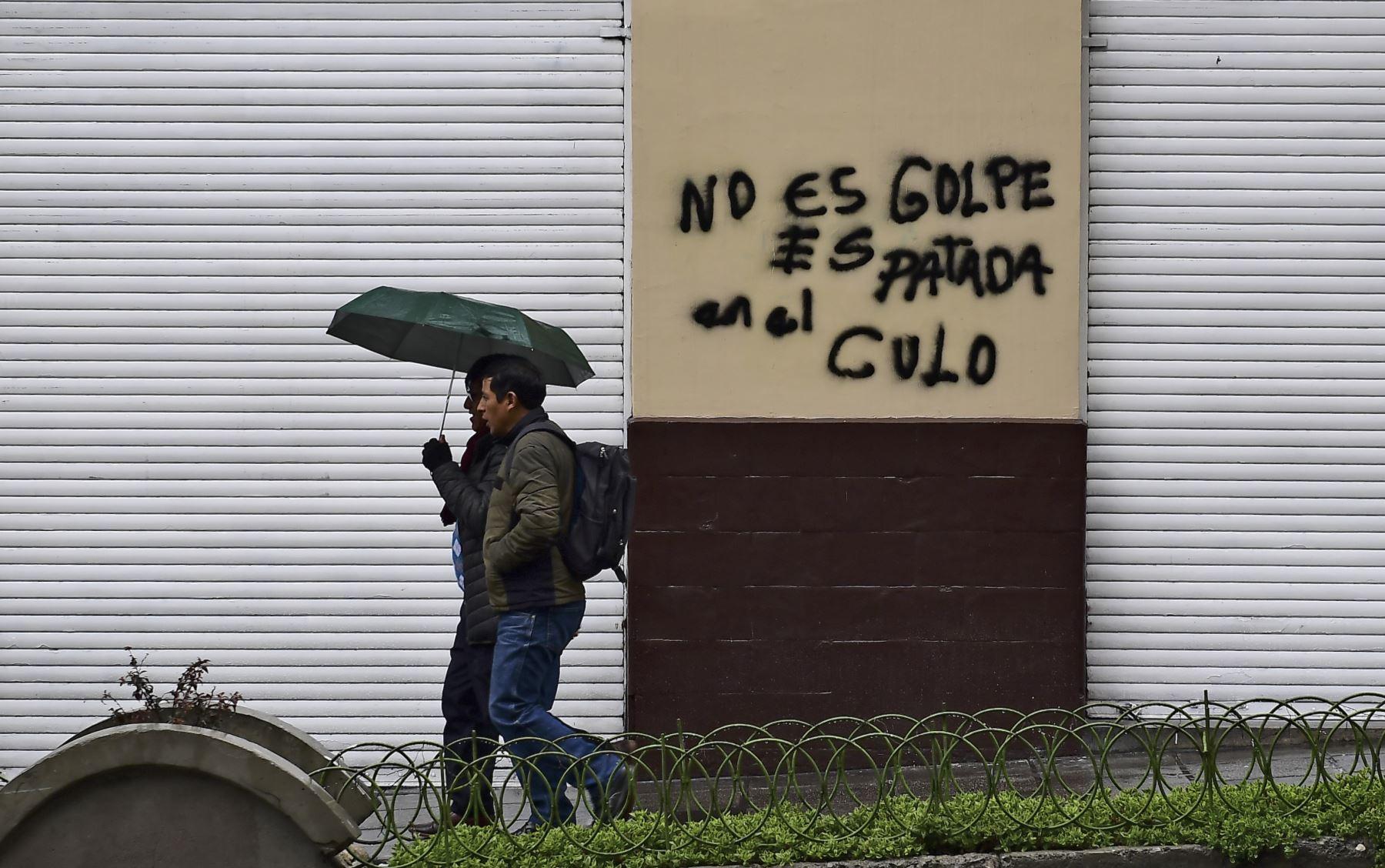 """Dos hombres pasan junto a una pared con un graffiti que dice """"No es un golpe de estado, es una patada en el culo"""" en La Paz. Foto: AFP"""