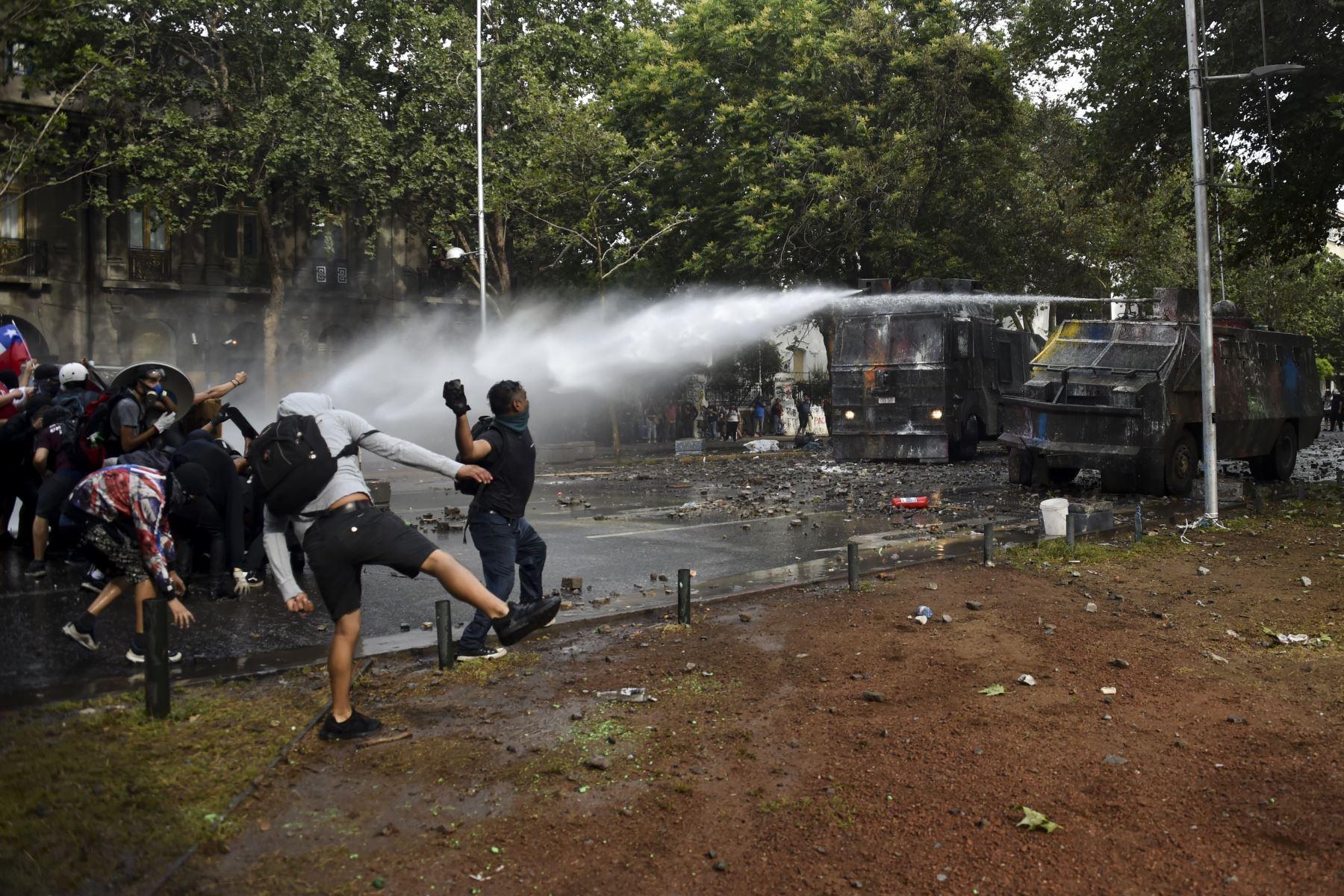Los manifestantes se enfrentan con la policía antidisturbios en Santiago de Chile en la cuarta semana de protestas contra el gobierno del presidente chileno Sebastián Piñera. Foto: AFP