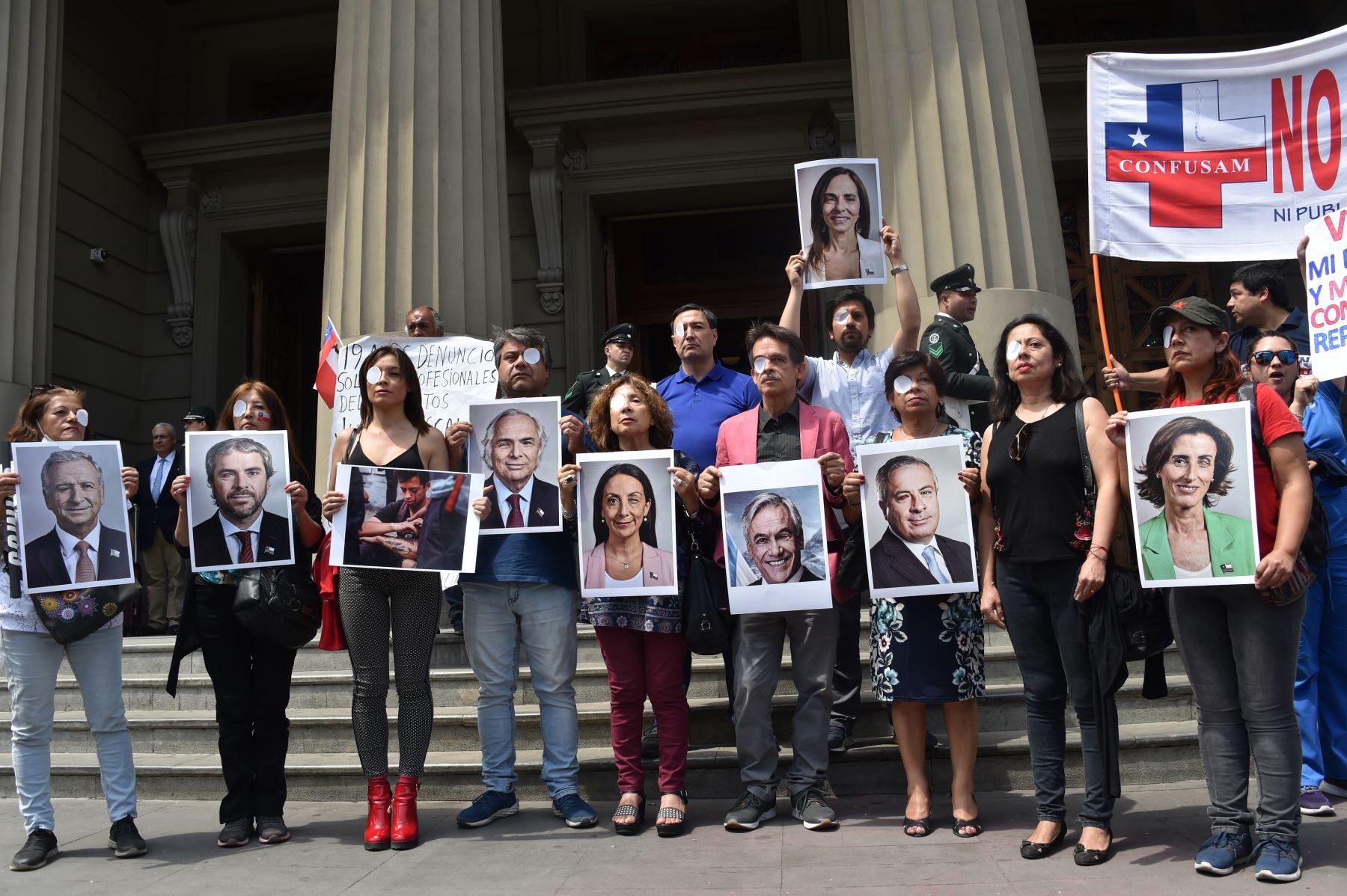 Los trabajadores de la salud protestan con retratos de ministros chilenos y de un manifestante al que le llegó un ojo de policía en la cuarta semana de protestas contra el gobierno del presidente chileno, Sebastián Piñera. Foto: AFP