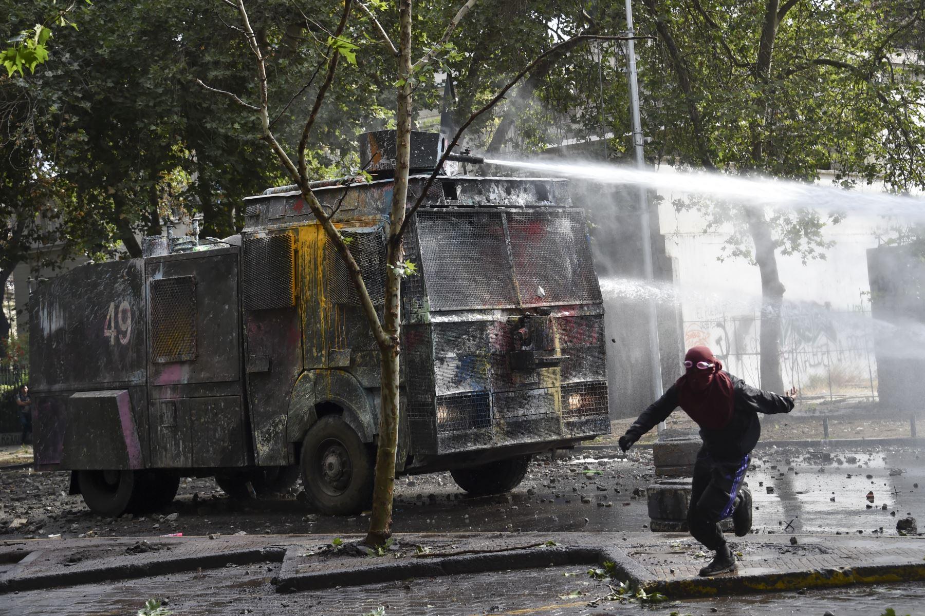 La policía antidisturbios rocía agua para dispersar a los manifestantes en Santiago en la cuarta semana de protestas contra el gobierno del presidente chileno Sebastián Piñera. Foto: AFP