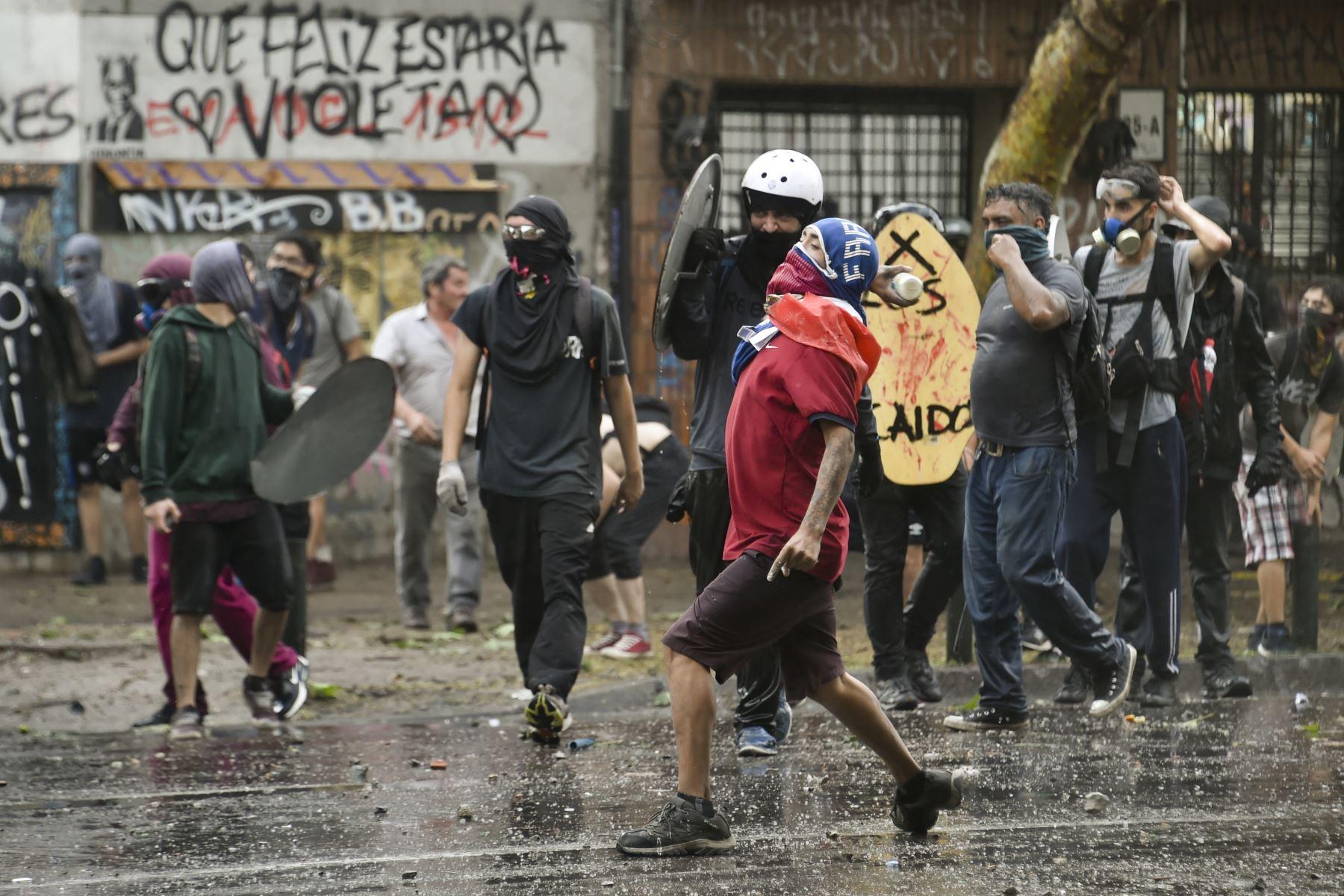 Los manifestantes se enfrentan con la policía antidisturbios en Santiago en la cuarta semana de protestas contra el gobierno del presidente chileno Sebastián Piñera. Foto: AFP
