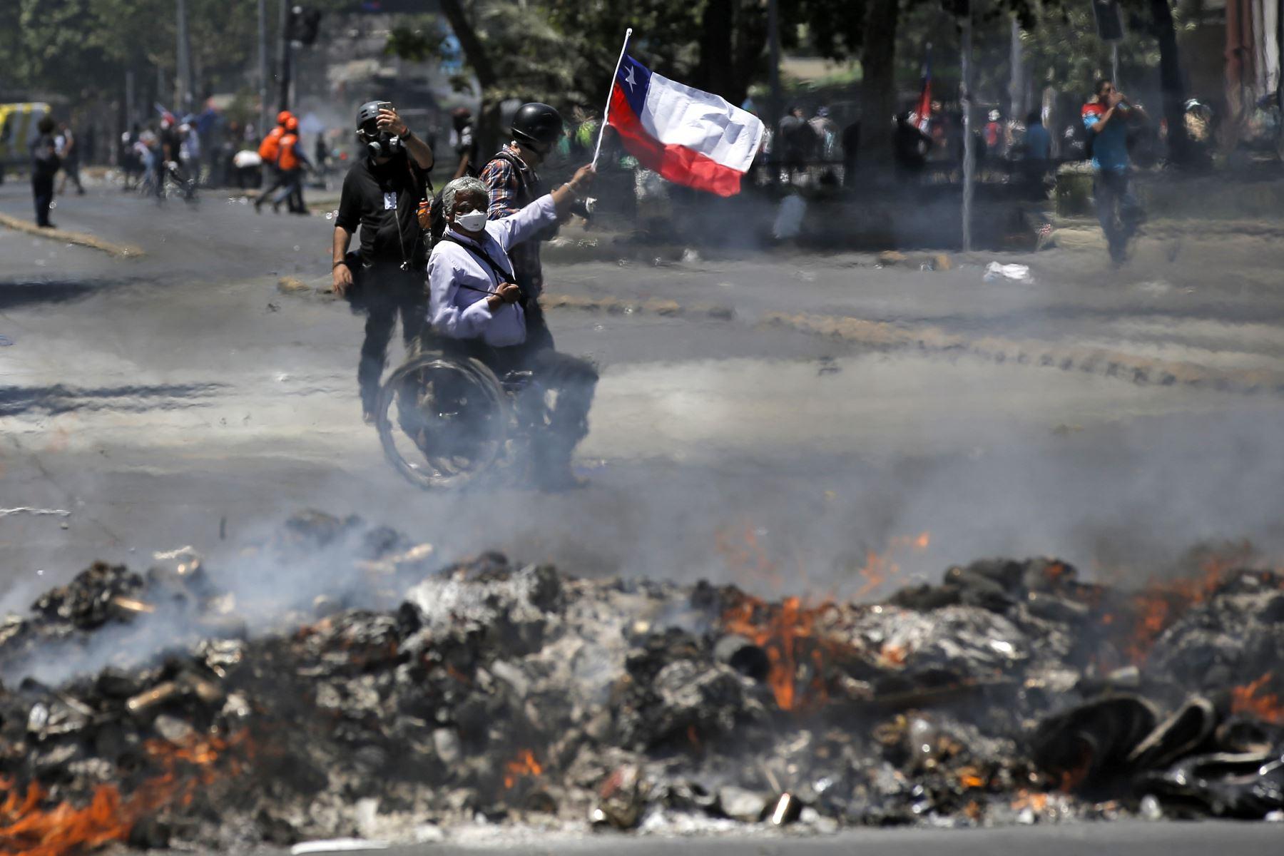 Un hombre en silla de ruedas ondea la bandera nacional chilena junto a una hoguera durante una protesta contra el gobierno de Sebastián Piñera en Santiago de Chile. Foto: AFP