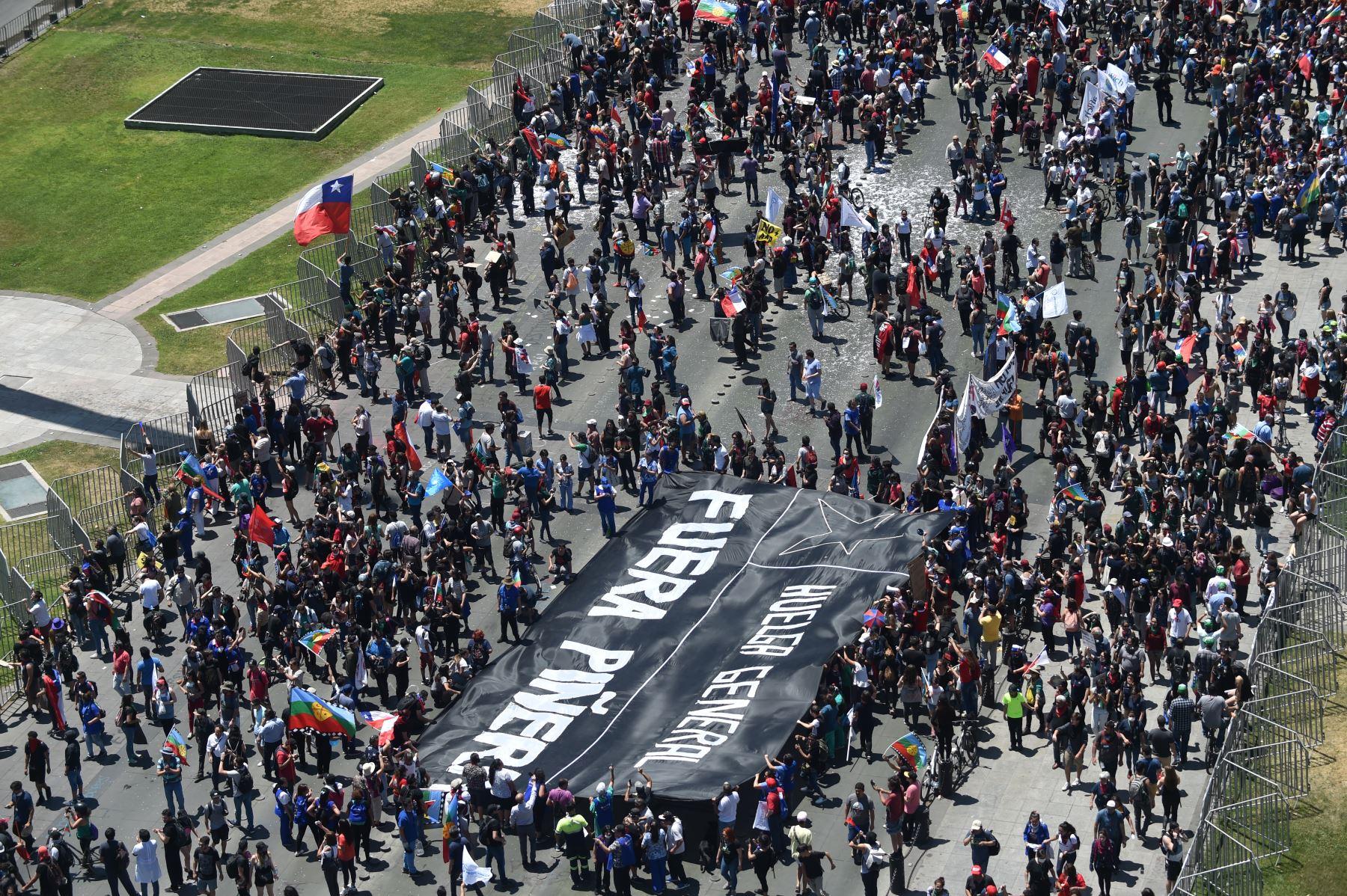 """Vista aérea de personas marchando contra el gobierno del presidente chileno Sebastián Piñera con una pancarta que decía """"Huelga general. Piña afuera"""" hacia el palacio presidencial de La Moneda en Santiago de Chile. Foto: AFP"""