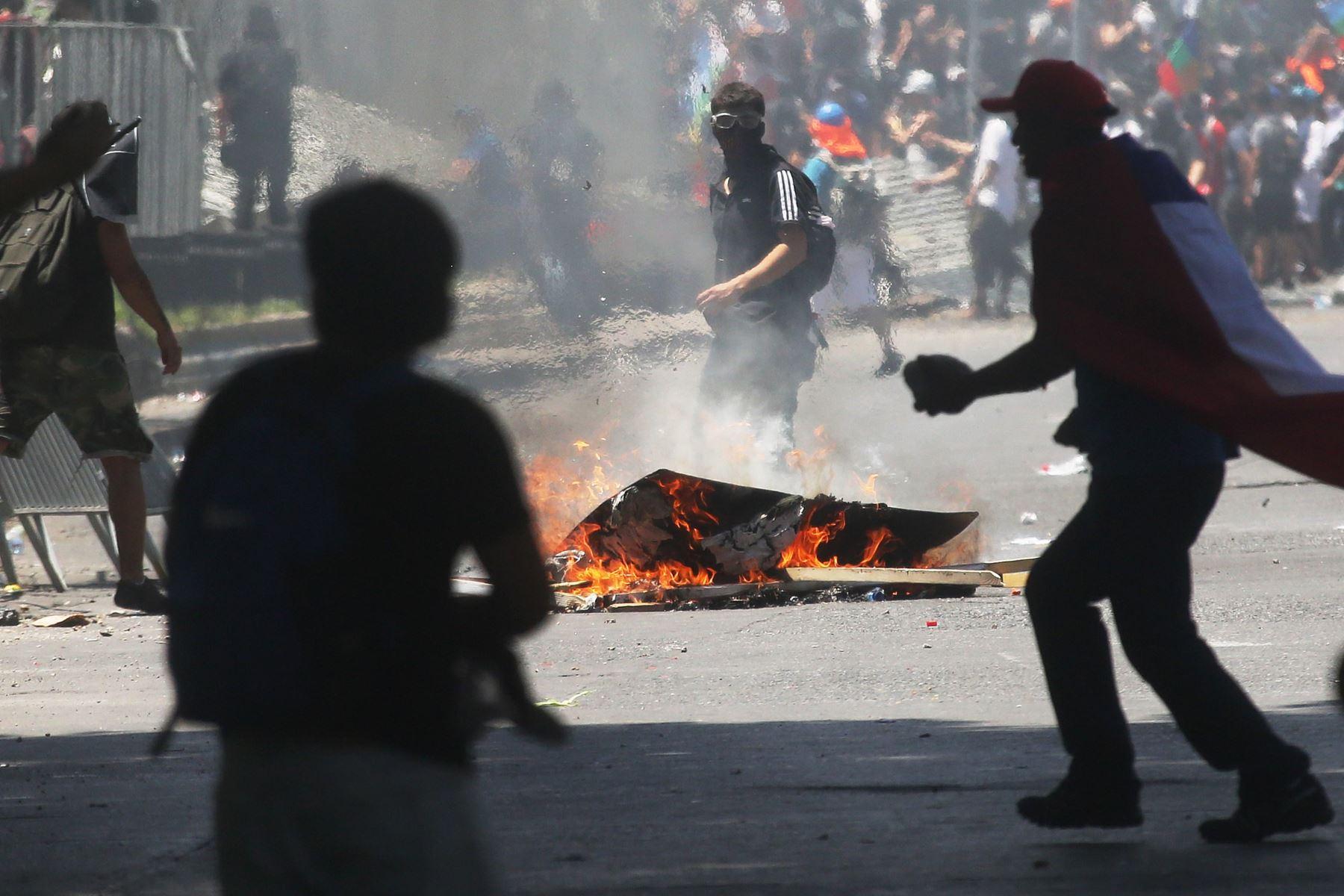 Un grupo de encapuchados se enfrenta a la policía, durante otra jornada de protestas, en Santiago de Chile. Foto: EFE