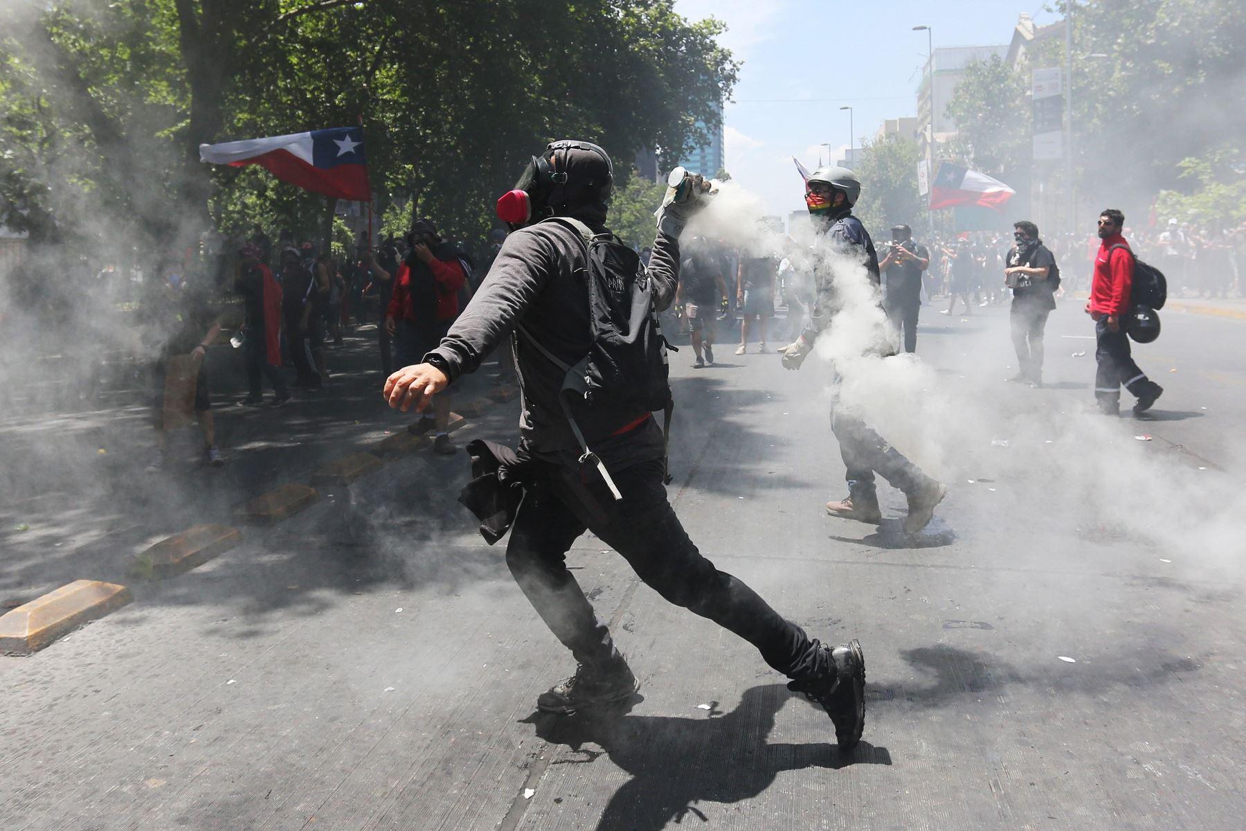 Un grupo de encapuchados se enfrenta a la policía , durante otra jornada de protestas, en Santiago de Chile. Foto: EFE
