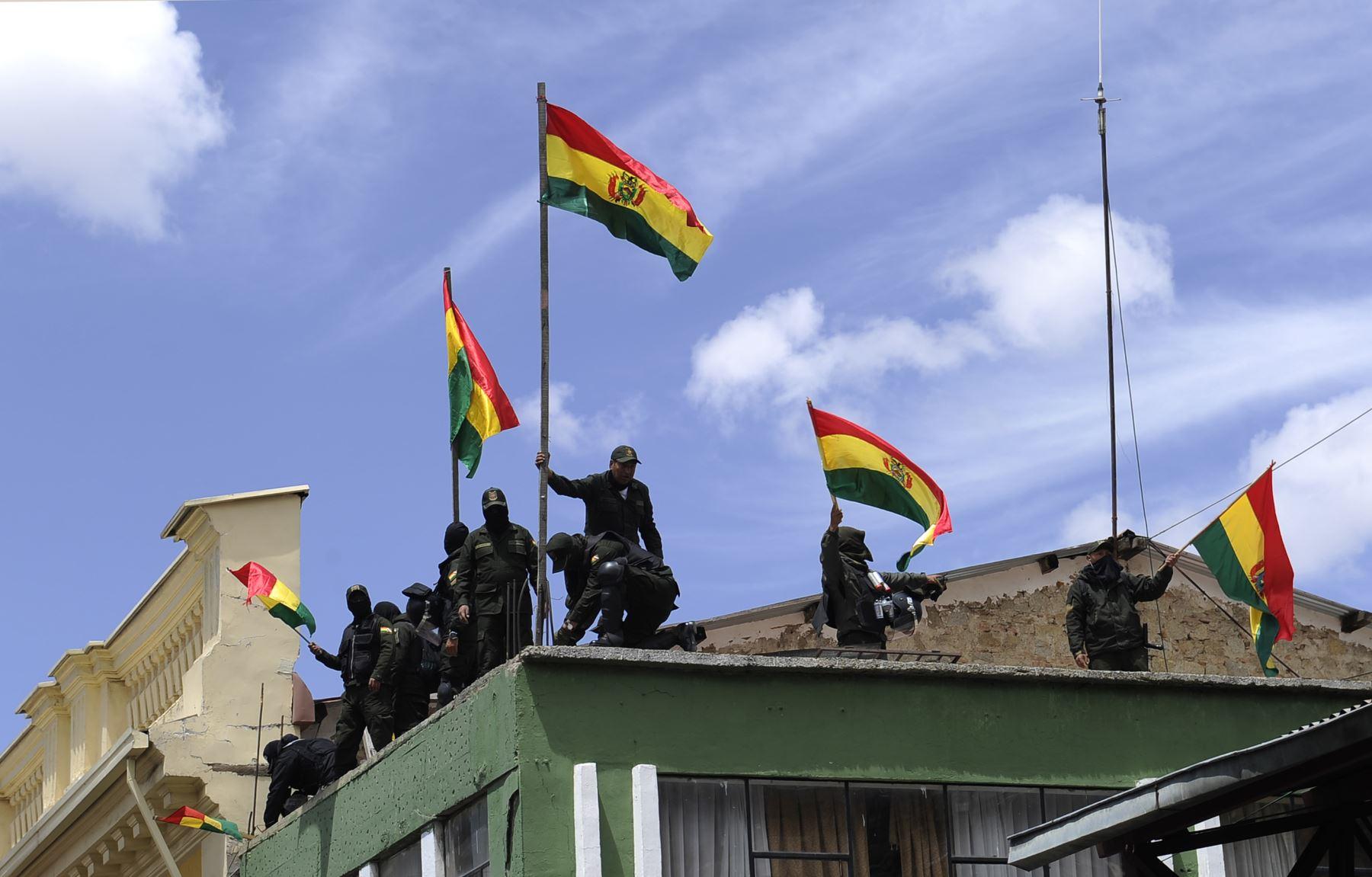 En esta foto de archivo tomada el 9 de noviembre de 2019, las fuerzas de la Unidad Táctica de Operaciones Especiales de la Policía (UTOP) muestran banderas bolivianas después de anunciar que se unirían a una rebelión. Foto: AFP