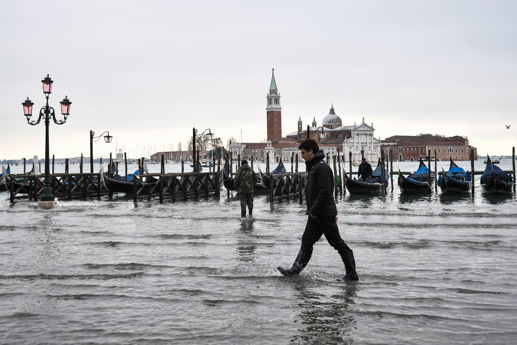 Un hombre camina por el terraplén inundado de Riva degli Schiavoni con la basílica de San Giorgio Maggiore en el fondo, después de un excepcional nivel de agua durante la marea alta en Venecia. Foto: AFP