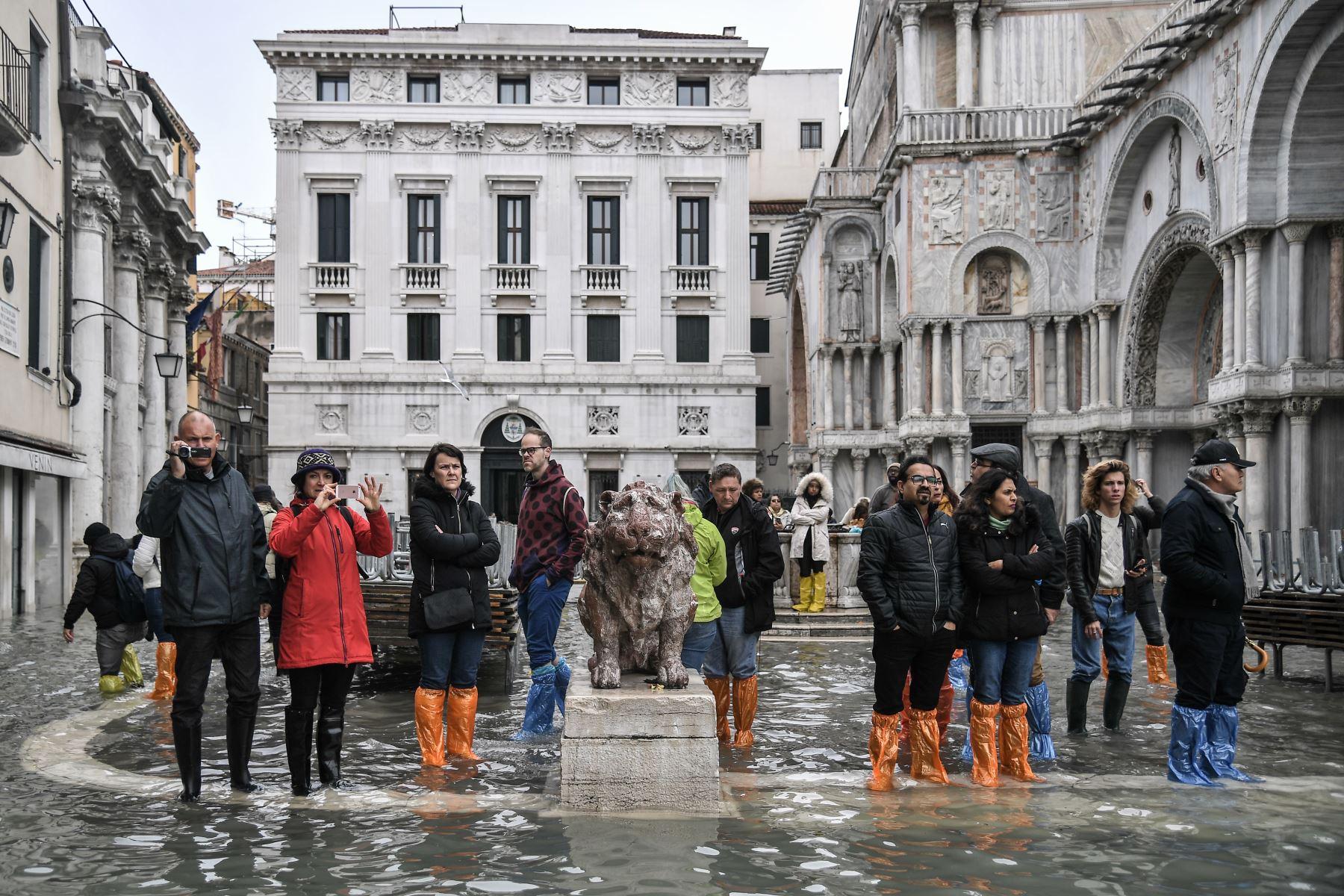 La gente mira desde la inundada Piazzetta dei Leoncini junto a la Basílica de San Marcos (R) y el Palazzo Patriarcale después de un excepcional nivel de agua durante la marea alta en Venecia. Foto: AFP
