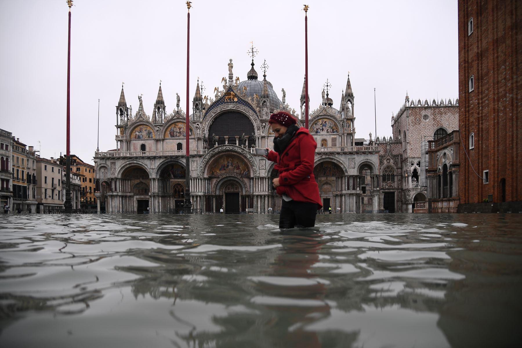 Una mujer cruza la inundada plaza de San Marcos junto a la basílica de San Marcos después de un excepcional nivel de agua durante la marea alta en Venecia. Foto: AFP