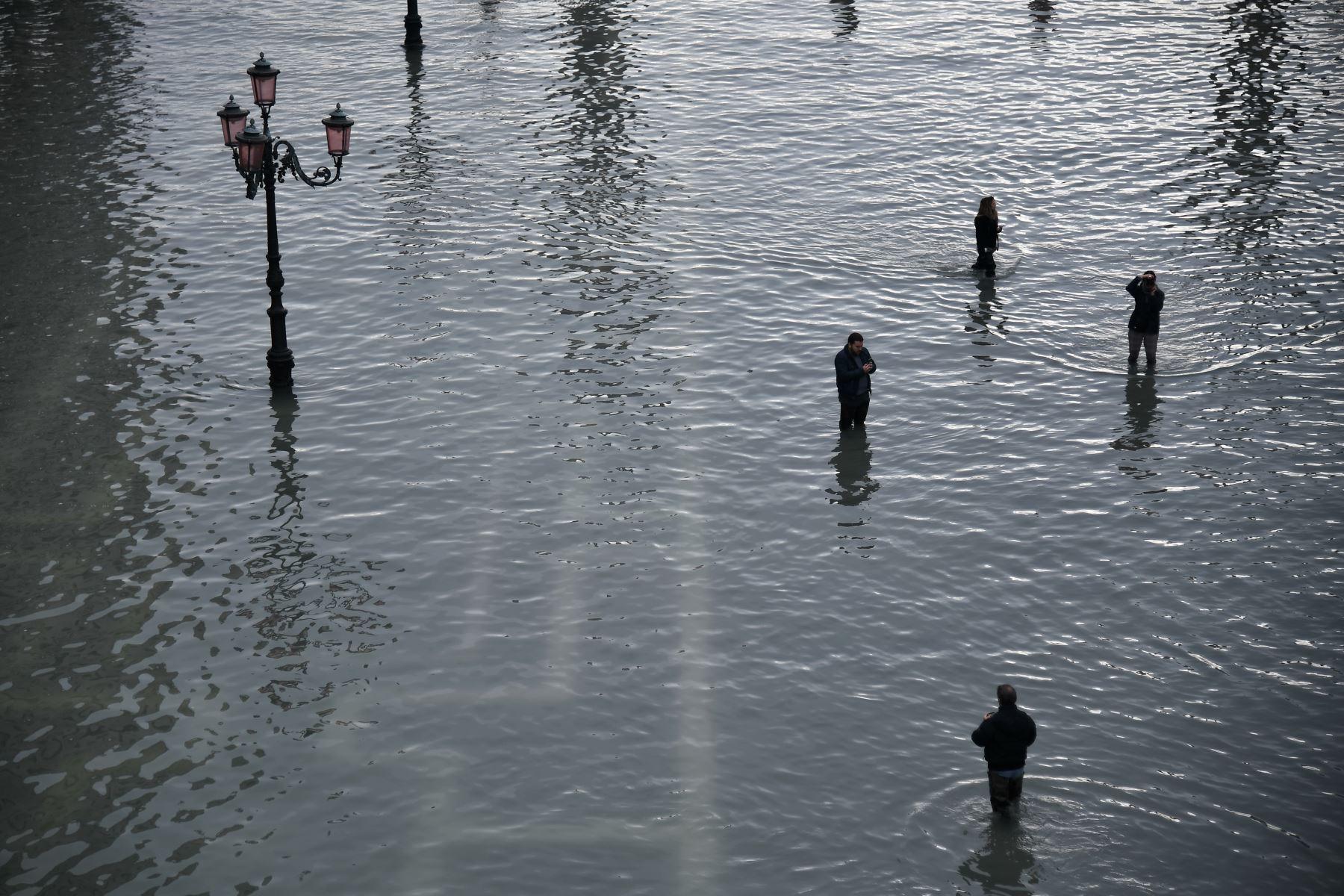 La gente camina y toma fotos en la inundada Plaza de San Marcos después de un excepcional nivel de agua durante la marea alta en Venecia. Foto: AFP