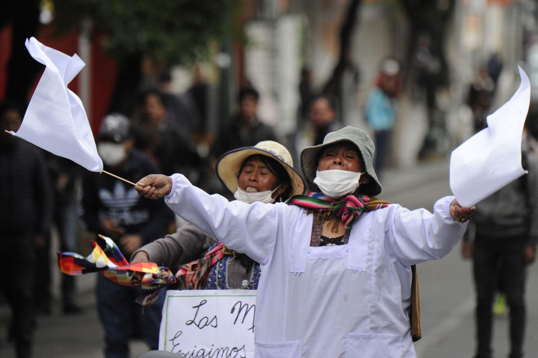 Los partidarios del ex presidente boliviano Evo Morales ondean banderas blancas durante los enfrentamientos con la policía antidisturbios luego de una protesta en La Paz Foto: AFP