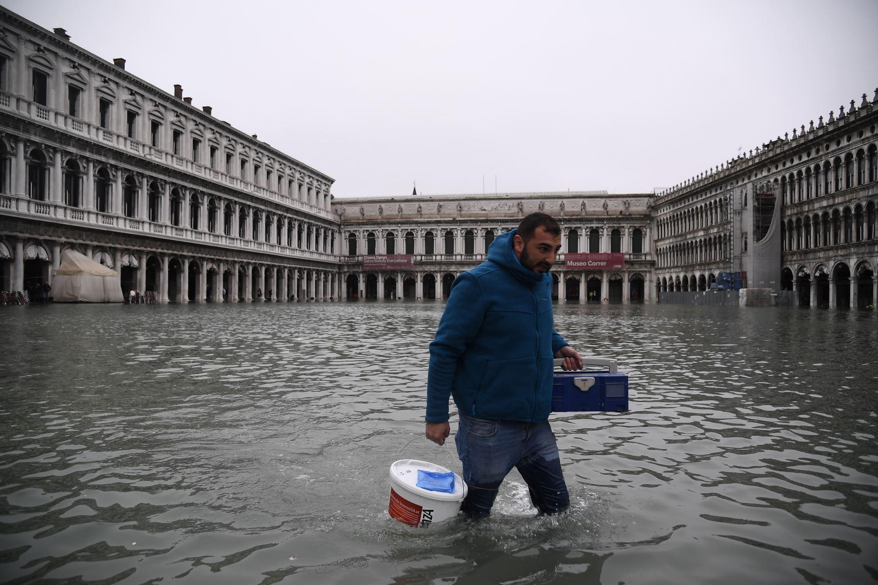 Un hombre con botas de muslo y equipo de transporte cruza la inundada plaza de San Marcos después de un excepcional nivel de agua durante la marea alta en Venecia. Foto: AFP