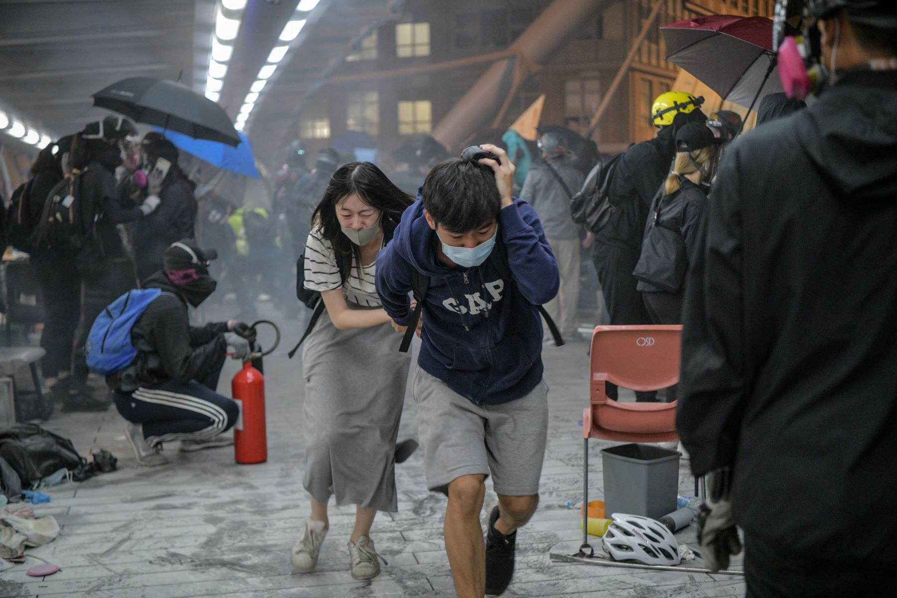Los agentes trataron de desalojar el túnel, pero los manifestantes se refugiaron tras paraguas (uno de los símbolos de la protesta) y prendieron fuego entre escombros, lo que generó pequeñas explosiones.Foto: AFP