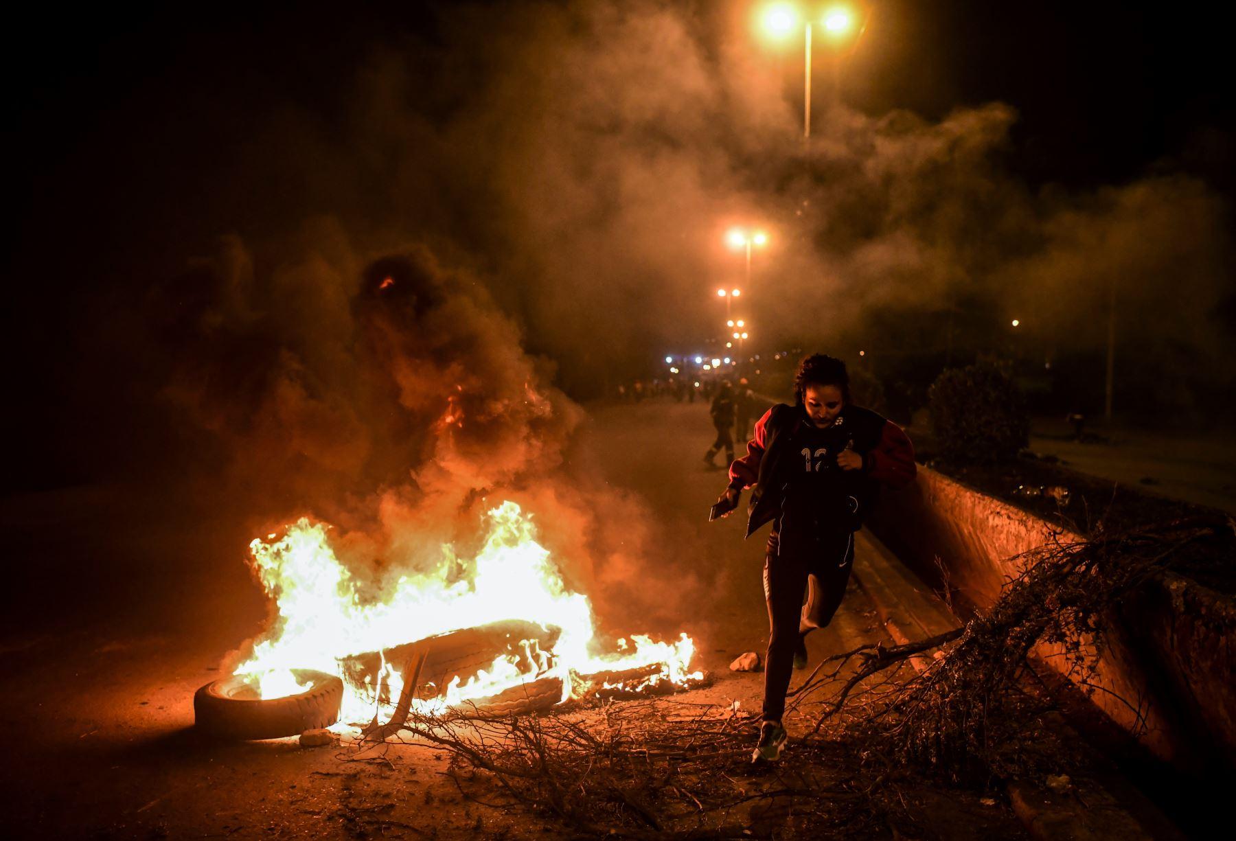 Una mujer cruza un bloqueo contra incendios establecido por partidarios del ex presidente boliviano Evo Morales en las afueras de Sacaba, provincia de Chapare, Cochabamba. Foto: AFP