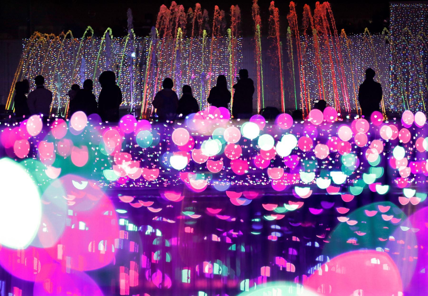 Varias personas observan la decoración navideña de un parque de atracciones de Tokio (Japón). Foto: EFE