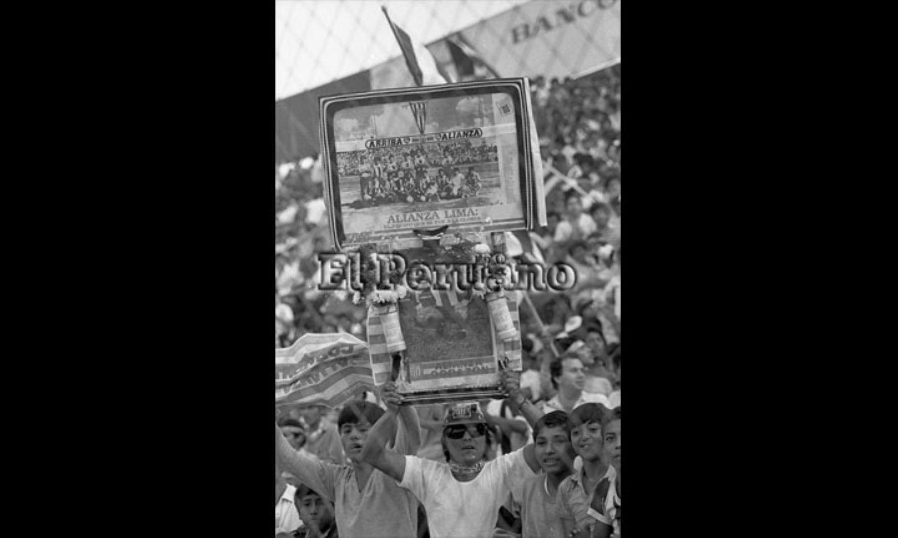 Lima - 17 diciembre 1987 / Un hincha de Alianza Lima portando imágenes de sus ídolos en el estadio Alejandro Villanueva. Alianza e Independiente de Avellaneda jugaron un partido internacional amistoso a beneficio de las víctimas del accidente aéreo donde desapareció el plantel principal del club íntimo.  Foto: ARCHIVO HISTORICO DE EL PERUANO.