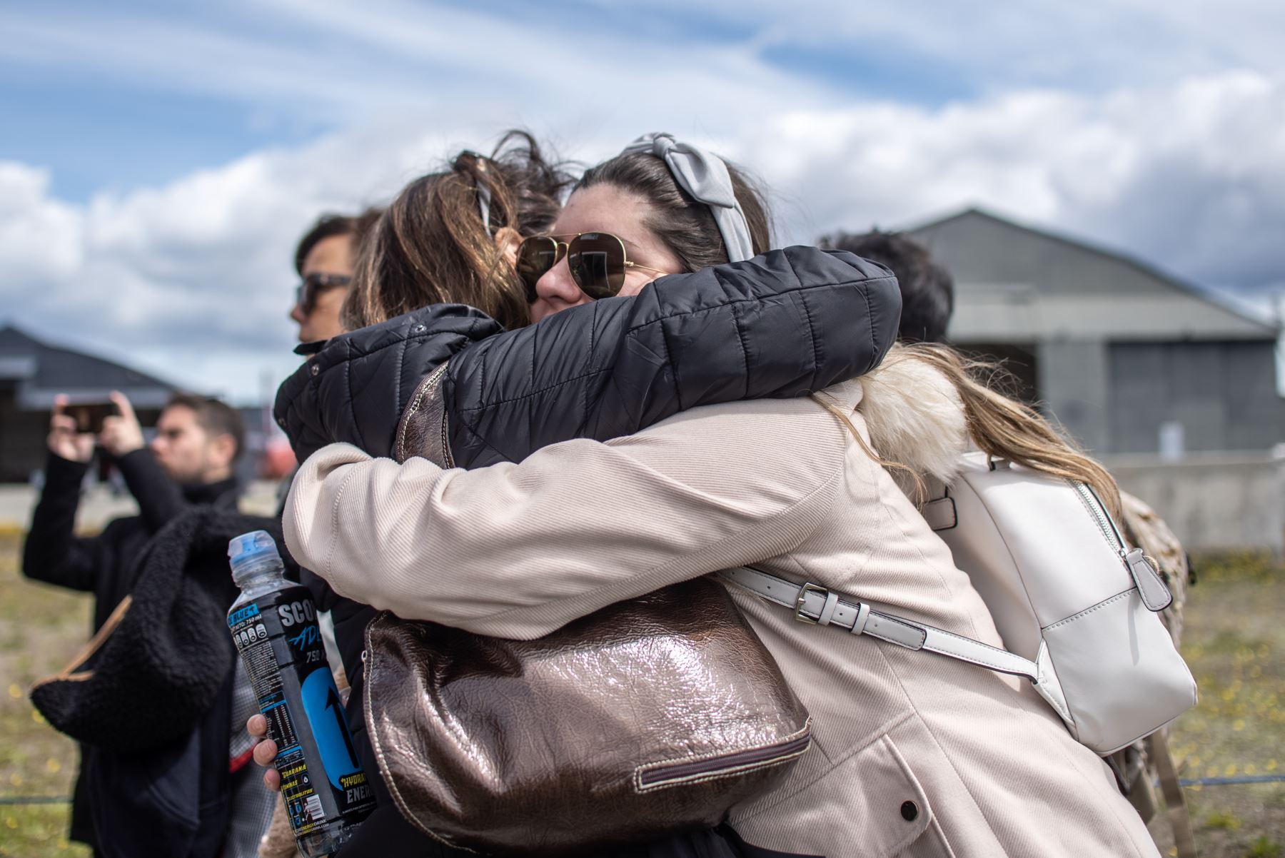Familiares a bordo del avión de carga Hércules C-130 de la Fuerza Aérea de Chile que desapareció en el mar entre el extremo sur de América del Sur y la Antártida, se abrazan en la base del ejército Chabunco en Punta Arenas, Chile. Foto: AFP