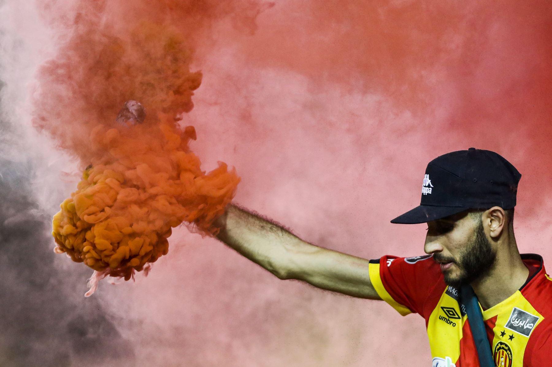 Los fanáticos de Esperance encienden bengalas mientras animan a su equipo durante el partido de fútbol de cuartos de final de la Copa Mundial de Clubes de la FIFA 2019 entre Hilal y Esperance de Tunis. Foto: AFP