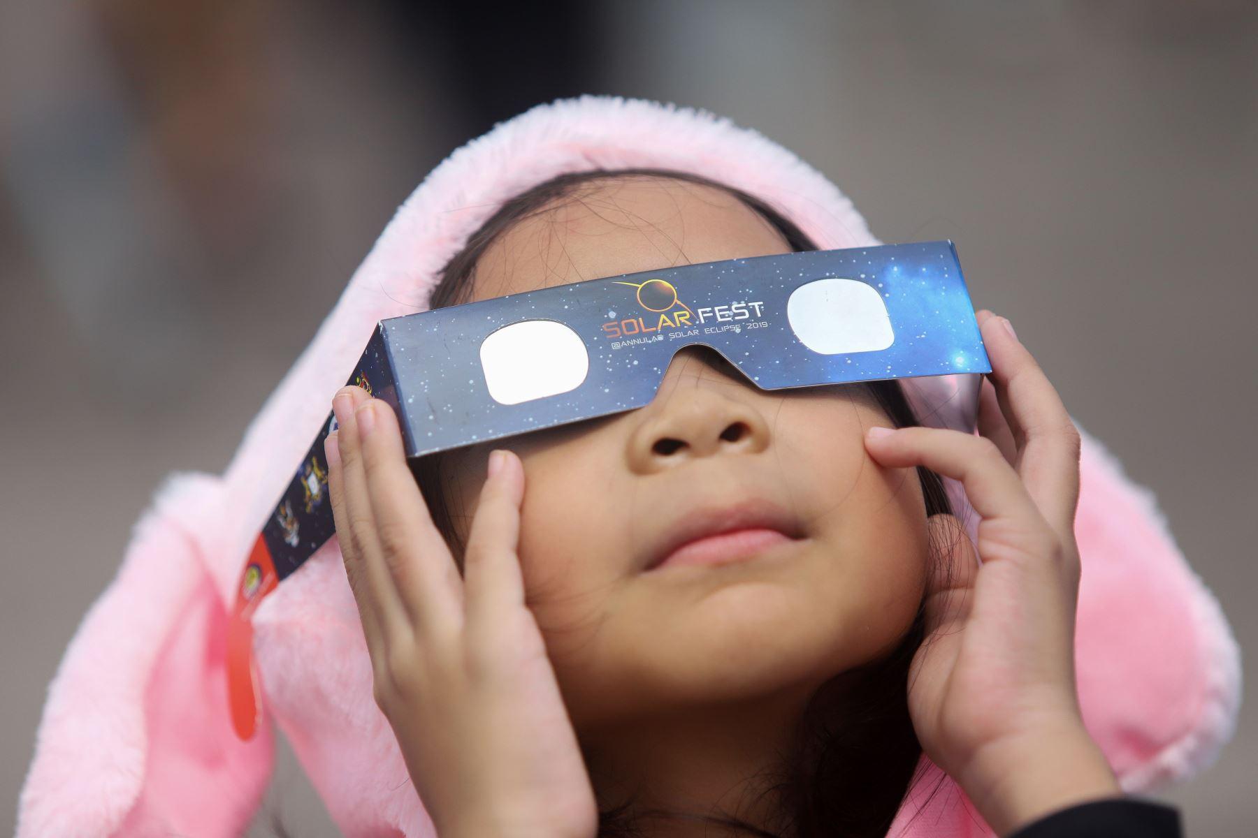 """Una niña usa lentes de filtro solar para mirar la luna mientras se mueve frente al sol en un eclipse solar de """"anillo de fuego"""" en Tanjung Piai, Malasia. Foto: AFP"""