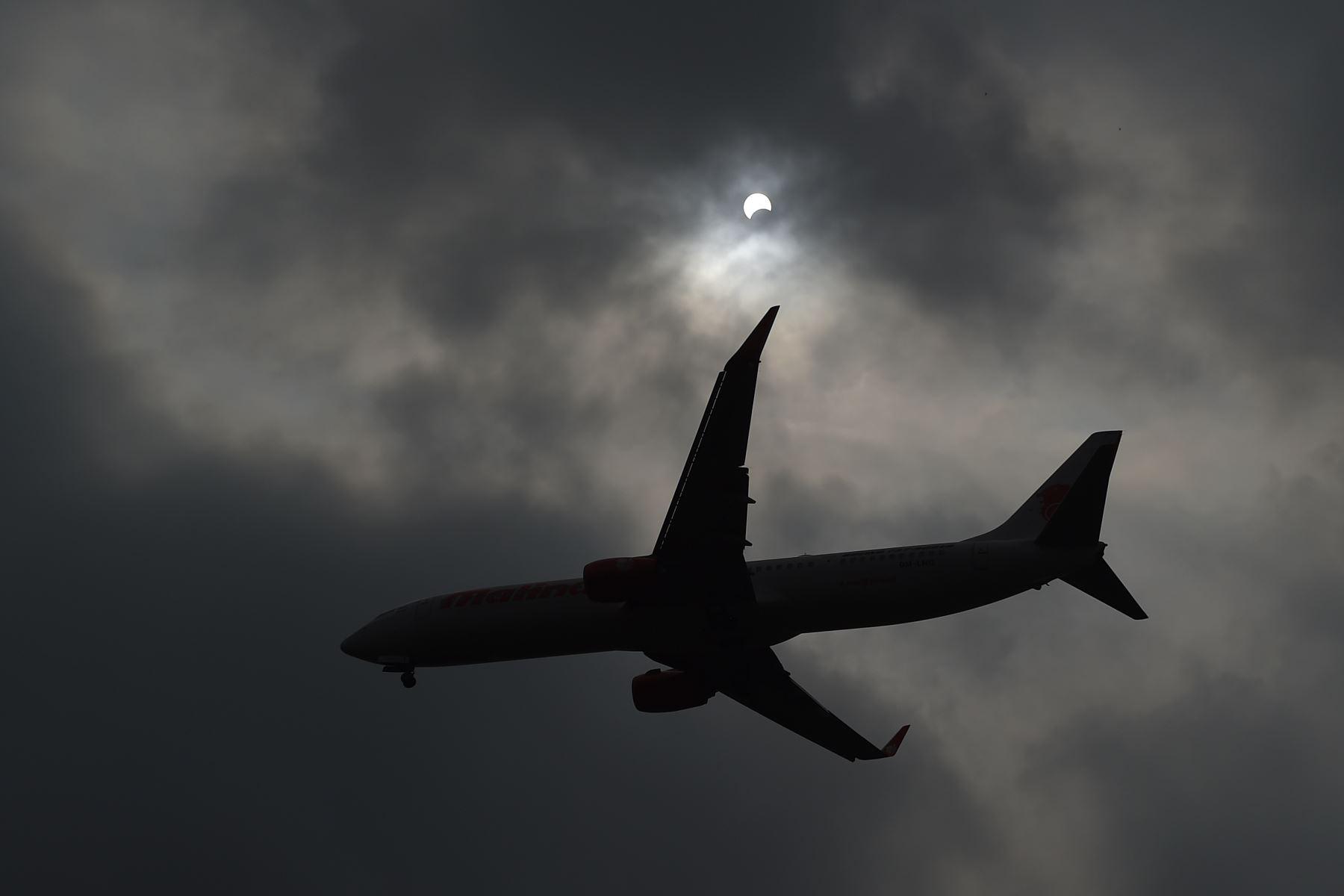 """Un avión pasa cuando la luna se mueve frente al sol en un eclipse solar de """"anillo de fuego"""" visto desde Hanoi el 26 de diciembre de 2019. Foto: AFP"""