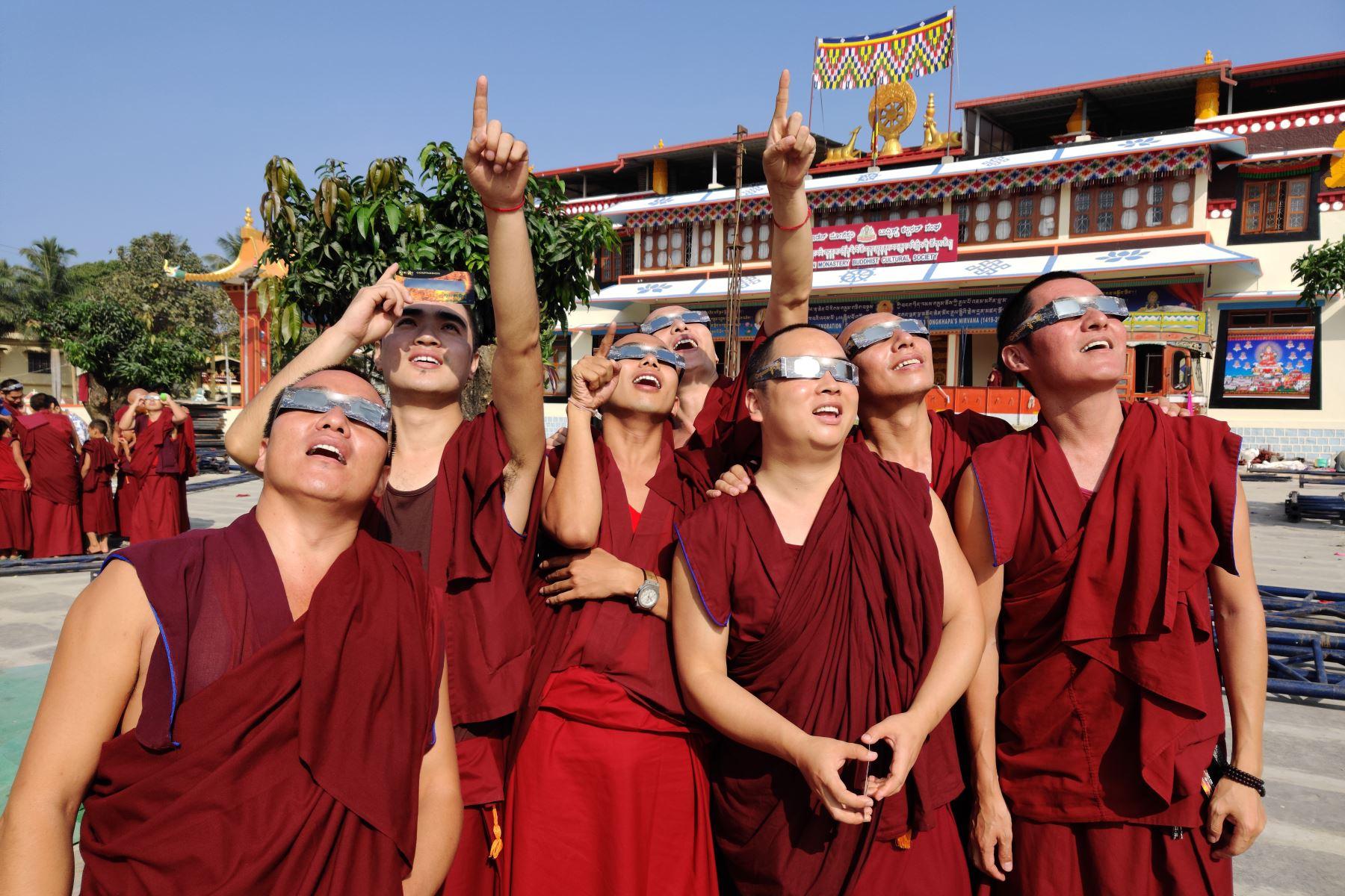 """Monjes con gafas de filtro solar observan un eclipse de """"anillo de fuego"""" en el monasterio de Gaden en una colonia tibetana en Teginkoppa, en el sur de la India. Foto: AFP"""
