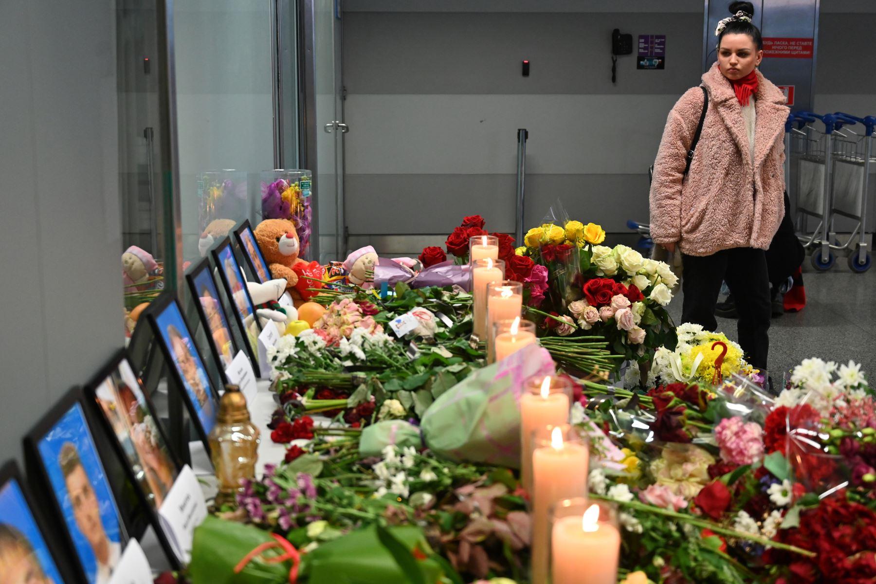 Una mujer se para frente a un monumento improvisado en el aeropuerto Boryspil a las afueras de Kiev, el 11 de enero de 2020, mientras rinde homenaje a las víctimas del Boeing 737-800 de Ukraine International Airlines que se estrelló cerca de la capital iraní, Teherán.  Foto: AFP