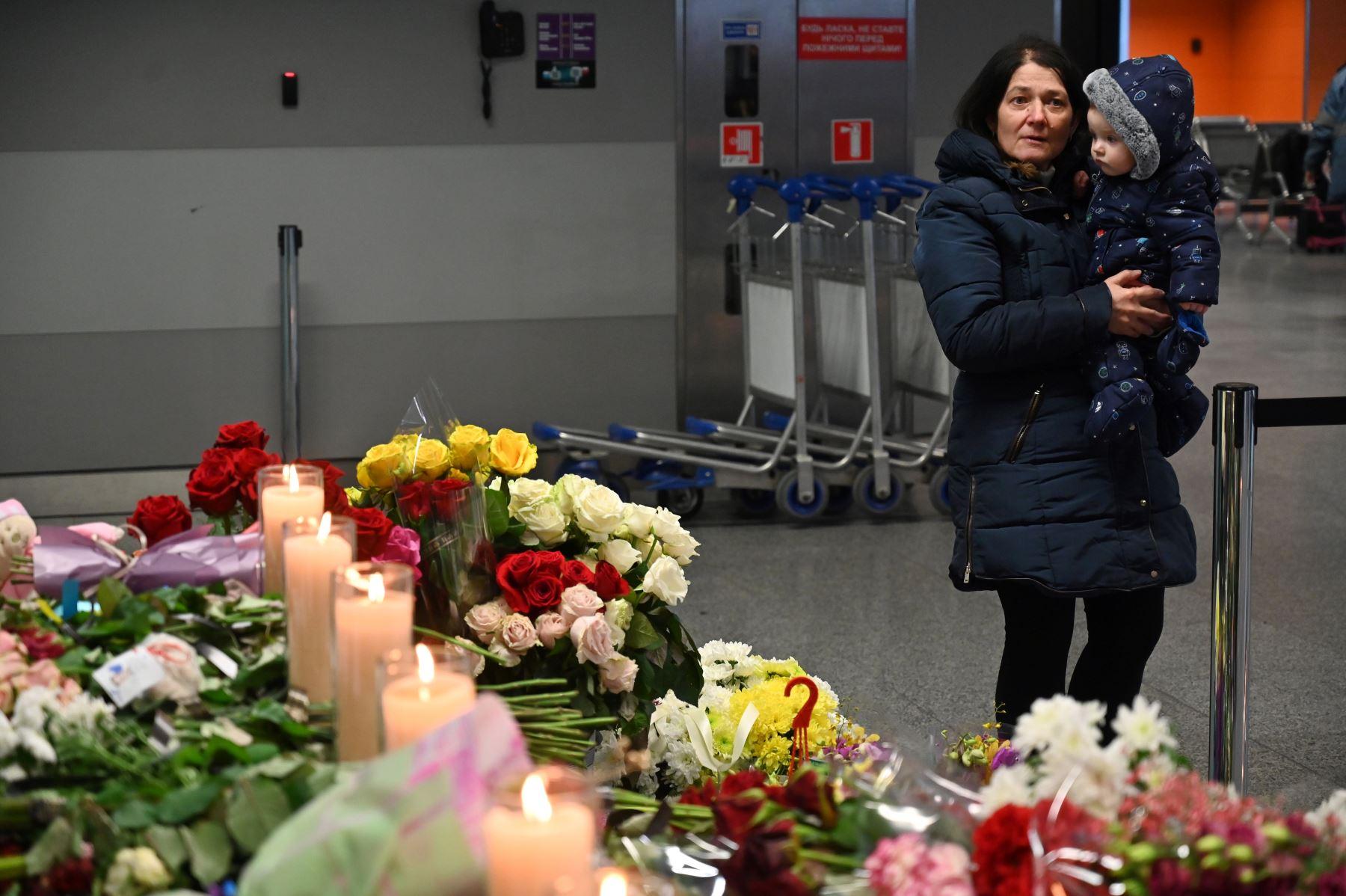 Una mujer reacciona mientras sostiene a un niño en el aeropuerto de Boryspil, en las afueras de Kiev, mientras rinde homenaje en un monumento improvisado para las víctimas del Boeing 737-800 de Ukraine International Airlines que se estrelló cerca de la capital iraní, Teherán.  Foto: AFP