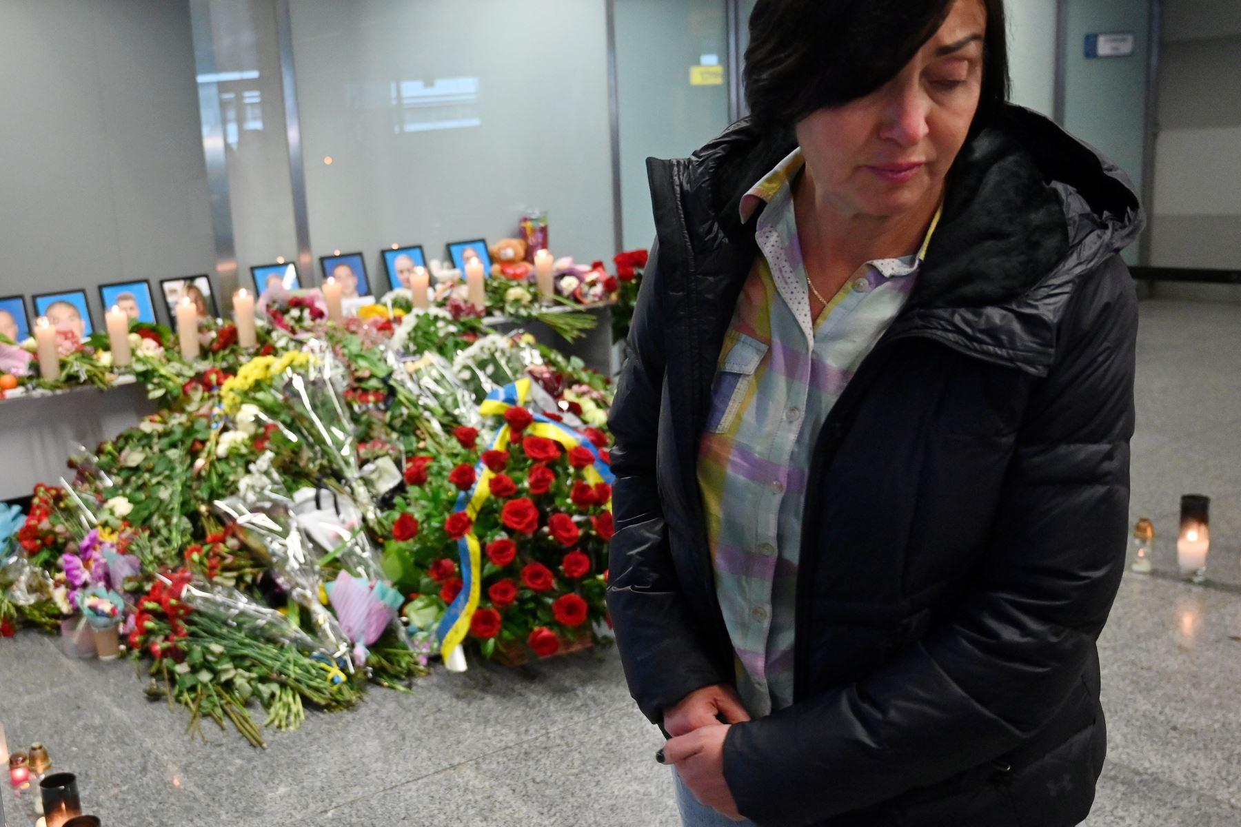 Una mujer reacciona en el aeropuerto de Boryspil, en las afueras de Kiev, mientras rinde homenaje en un monumento improvisado a las víctimas del Boeing 737-800 de Ukraine International Airlines que se estrelló cerca de la capital iraní, Teherán. Foto: AFP