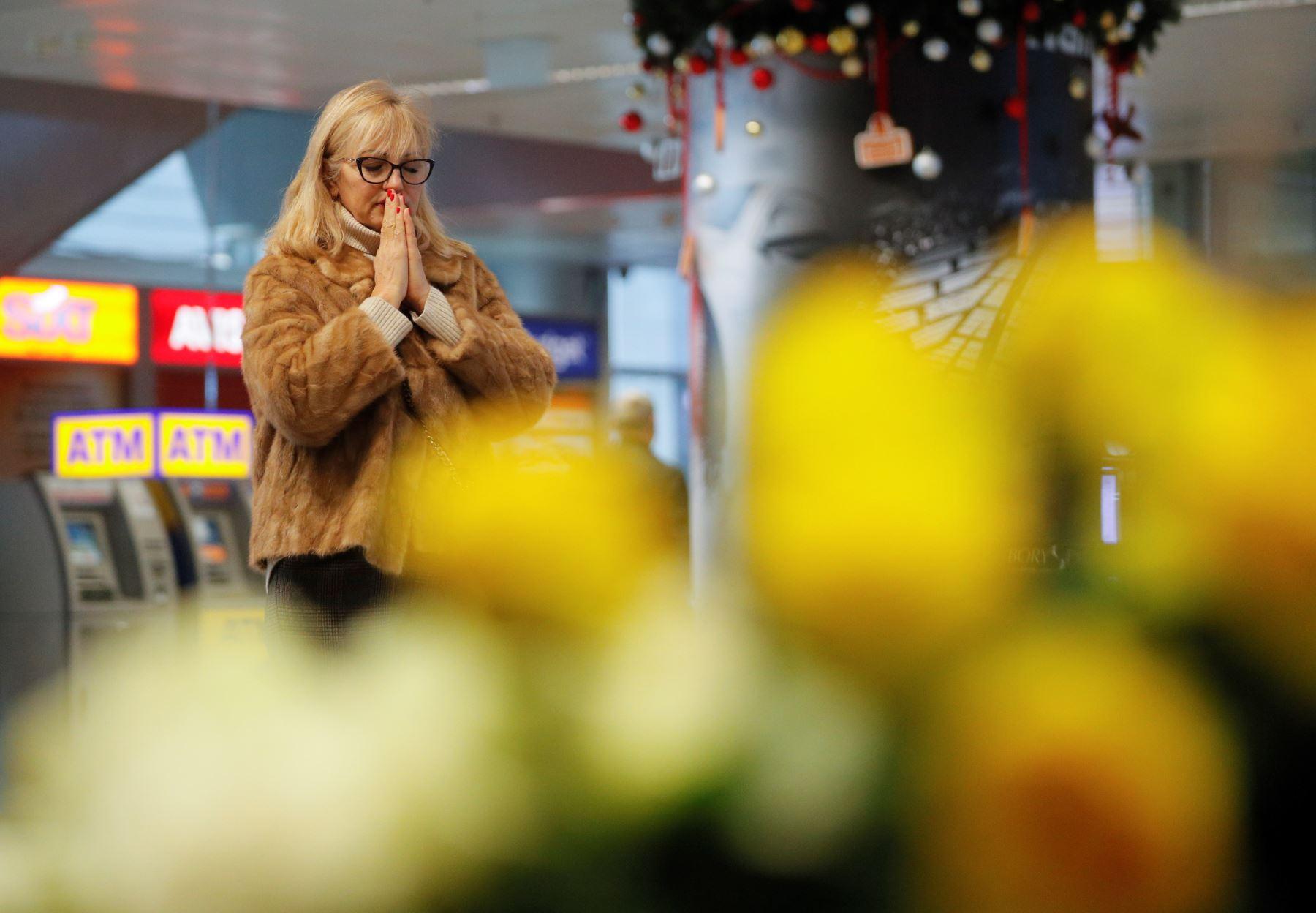 La gente reacciona mientras rinden homenaje cerca de los retratos de los miembros de la tripulación del vuelo PS752 de Ukraine International Airlines en el aeropuerto internacional de Boryspil en Kiev, Ucrania.