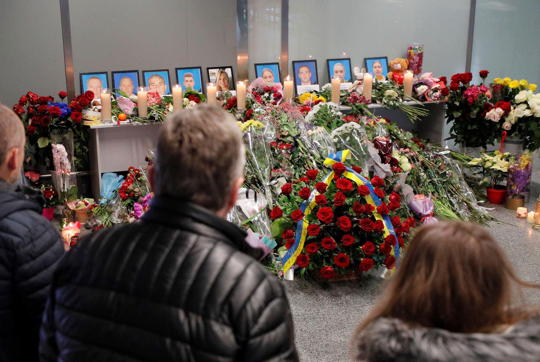 La gente rinde homenaje cerca de los retratos de los miembros de la tripulación del vuelo PS752 de Ukraine International Airlines en el aeropuerto internacional de Boryspil en Kiev, Ucrania. Foto: EFE