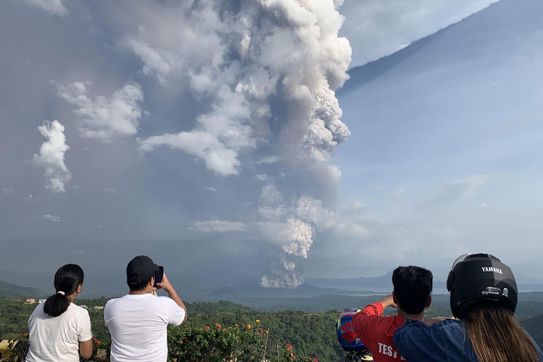 La gente toma fotos de una explosión freática del volcán Taal vista desde la ciudad de Tagaytay en la provincia de Cavite, al suroeste de Manila. Foto: AFP