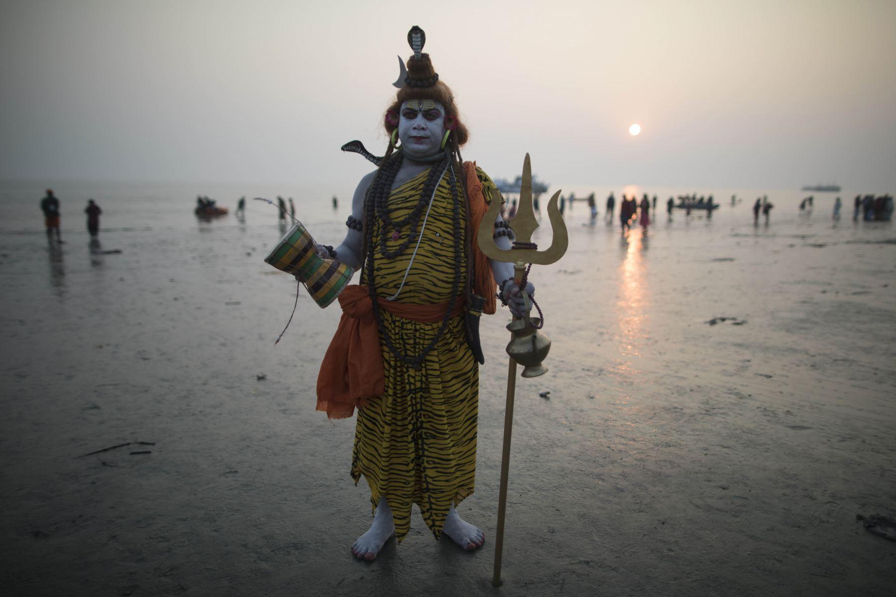 Un devoto hindú vestido como Lord Shiva se para en la playa mientras otros se bañan en la bahía de Bengala durante el Gangasagar Mela, en la isla Sagar, a unos 150 kilómetros al sur de Calcuta. Foto: AFP