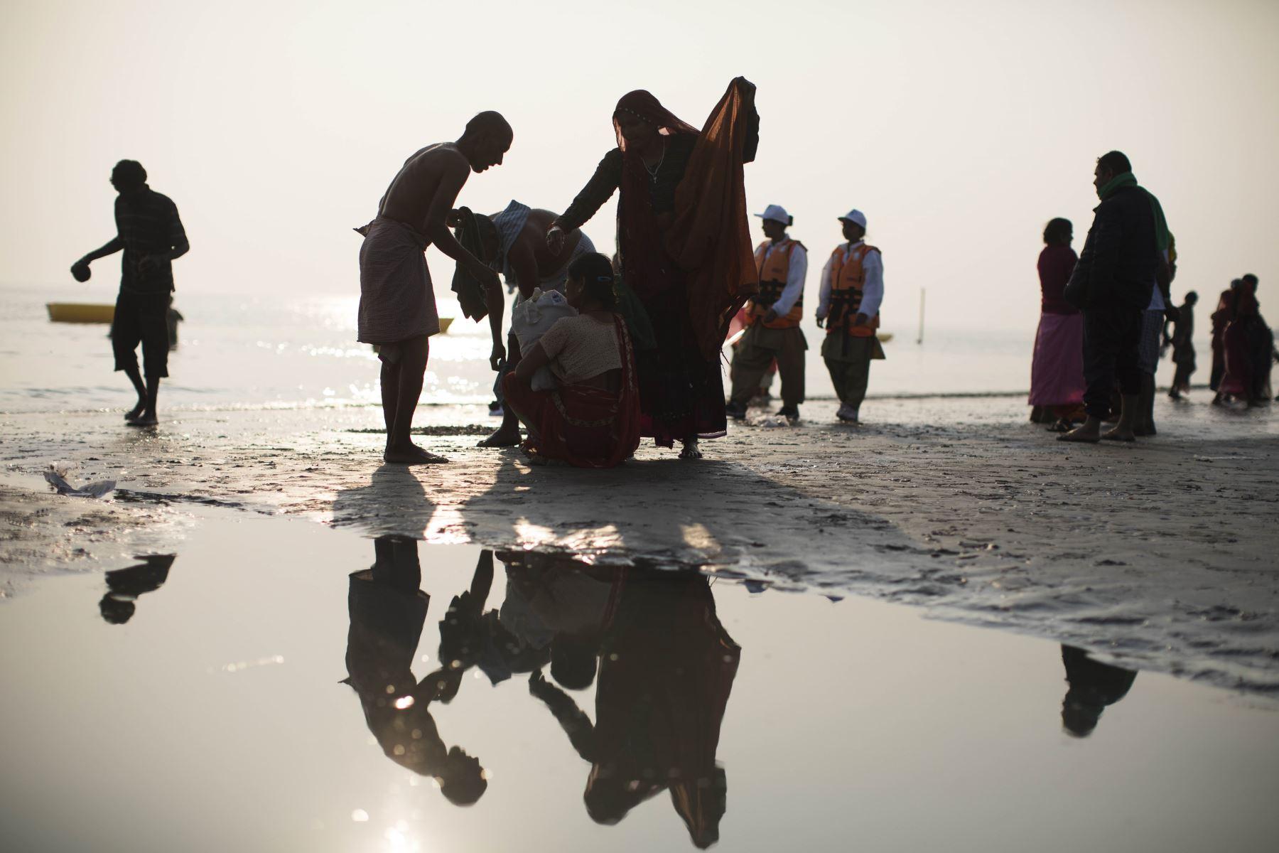 Devotos hindúes se visten después de darse un baño sagrado en la Bahía de Bengala durante el Gangasagar Mela. Foto: AFP