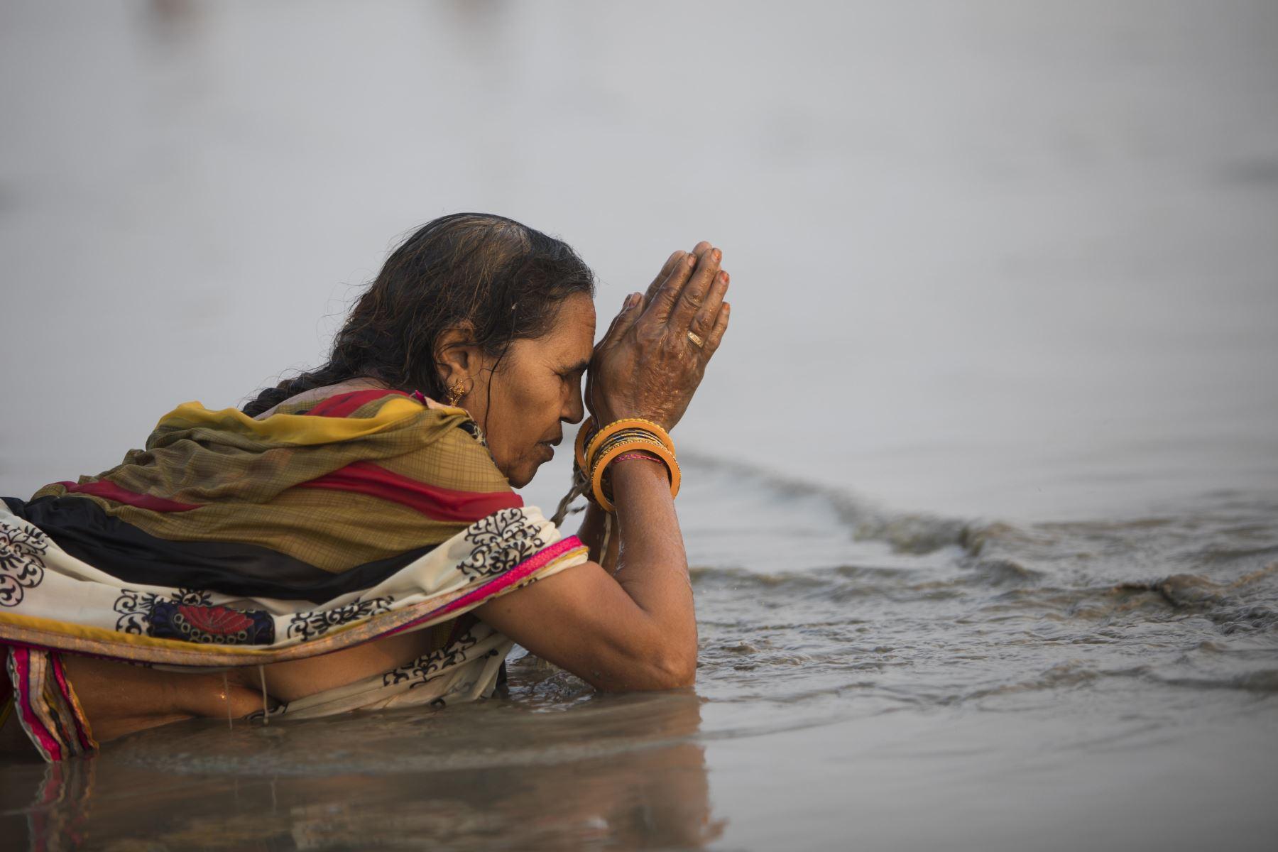 Un devoto hindú realiza un ritual antes de darse un baño sagrado en la Bahía de Bengala durante el Gangasagar Mela. Foto: AFP