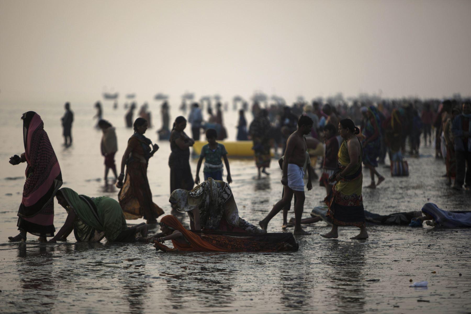 Devotos hindúes realizan rituales antes de darse un baño sagrado en la Bahía de Bengala durante el Gangasagar Mela. Foto: AFP